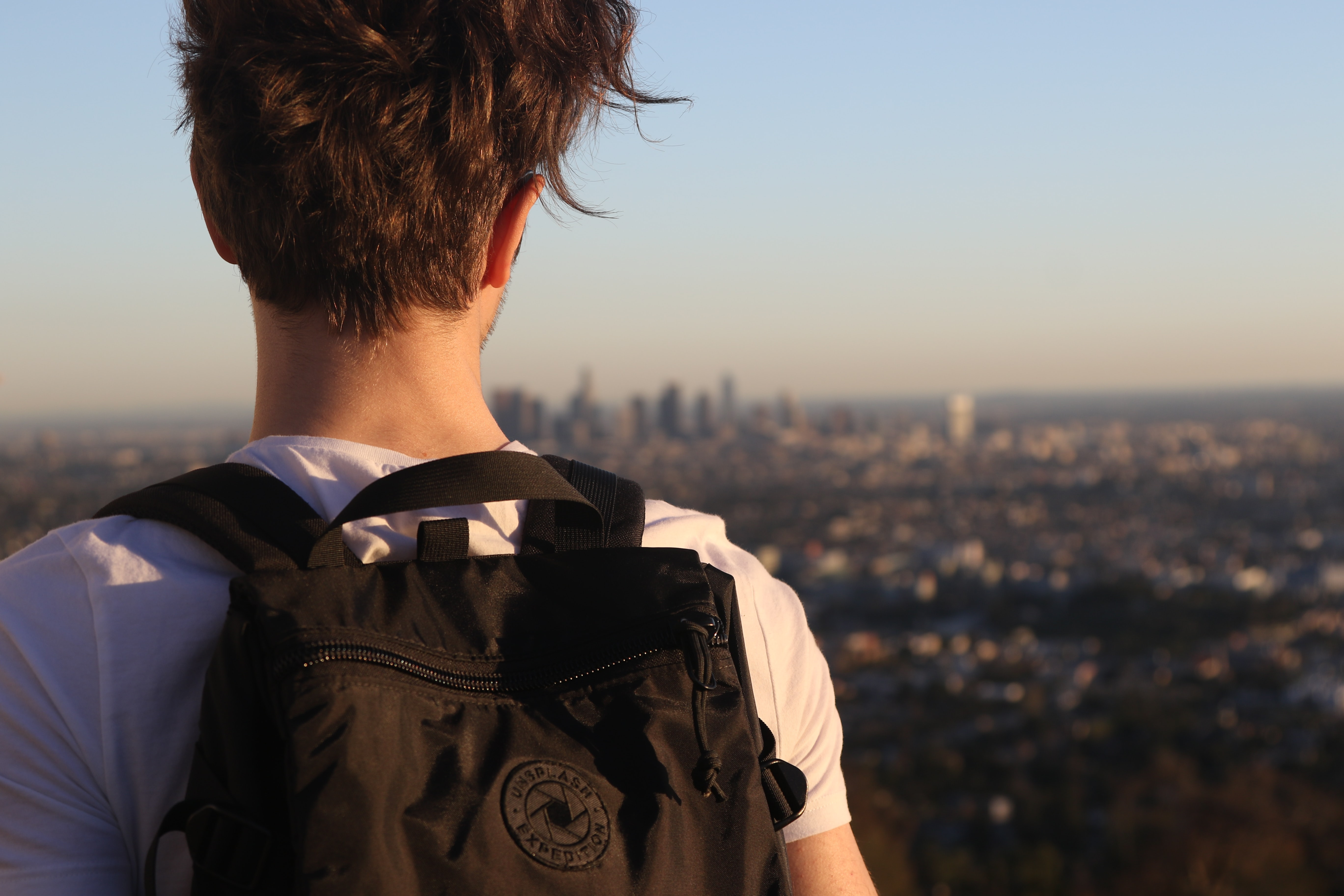 Standing behind a man wearing a backpack looking out at the Los Angeles skyline
