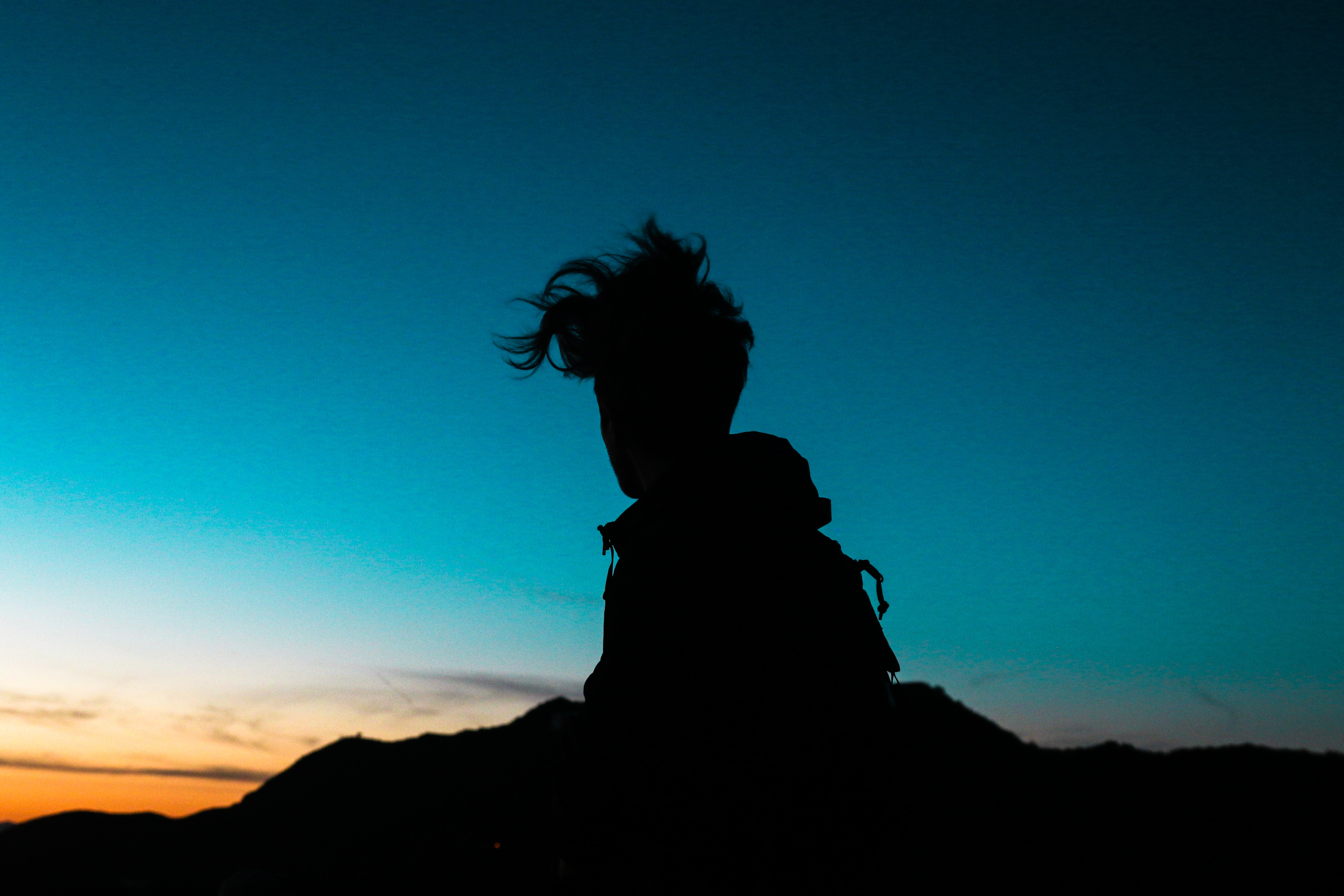 A person with their hair flying in the winds silhouette against the sky at sunset in Los Angeles