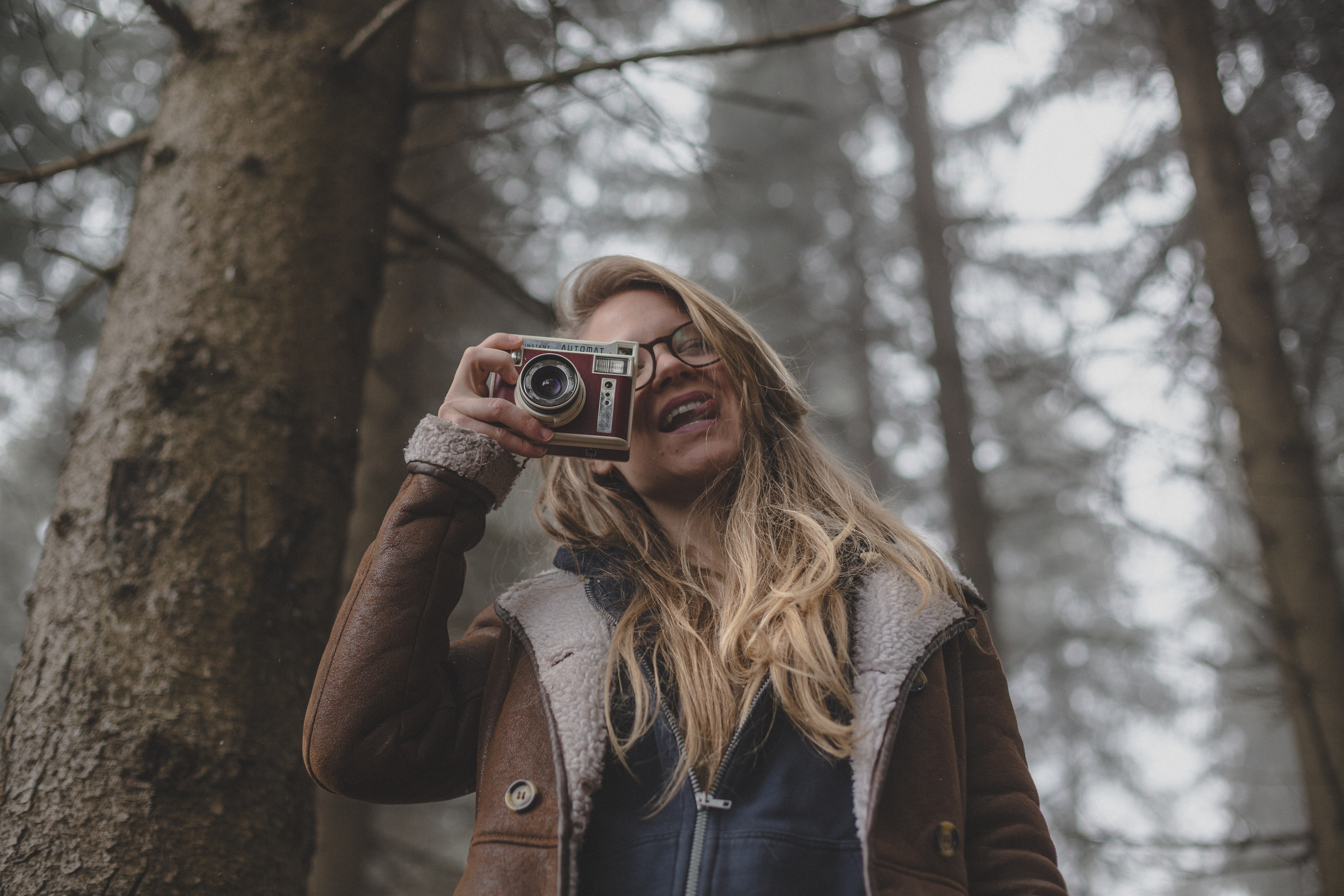 Smiling woman in glasses and coat takes a photo in a forest