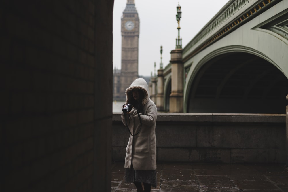woman standing beside brown wall