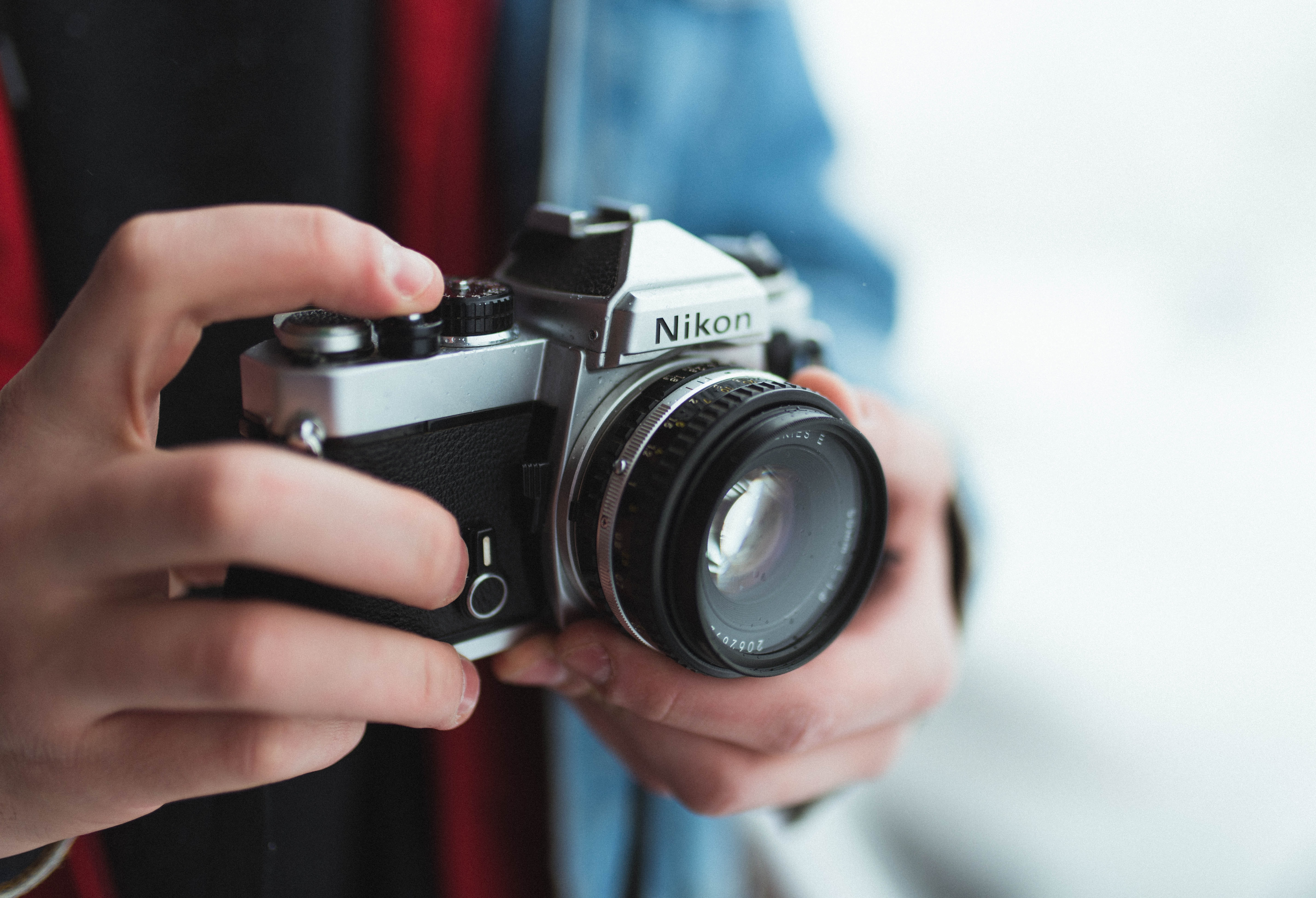 person holding black and gray Nikon DSLR camera