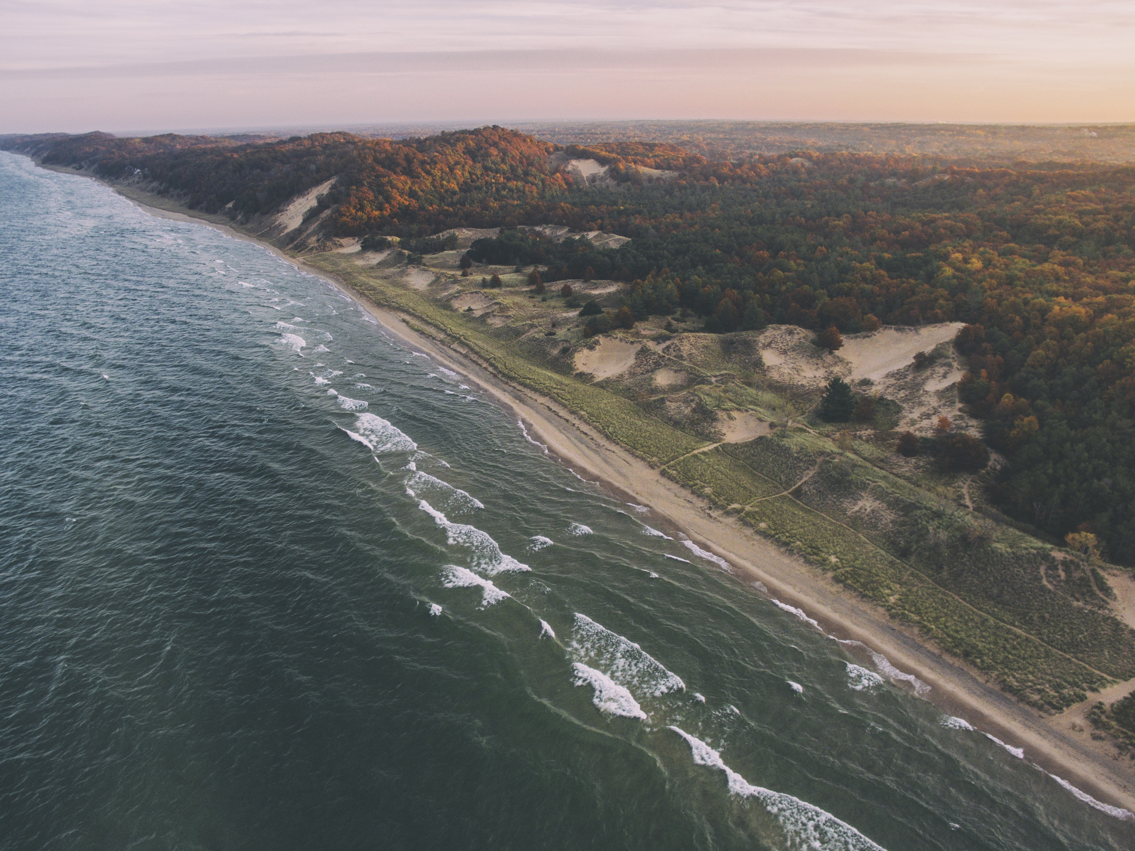 A drone shot of a lake and forest in autumn in Holland, Michigan, United States