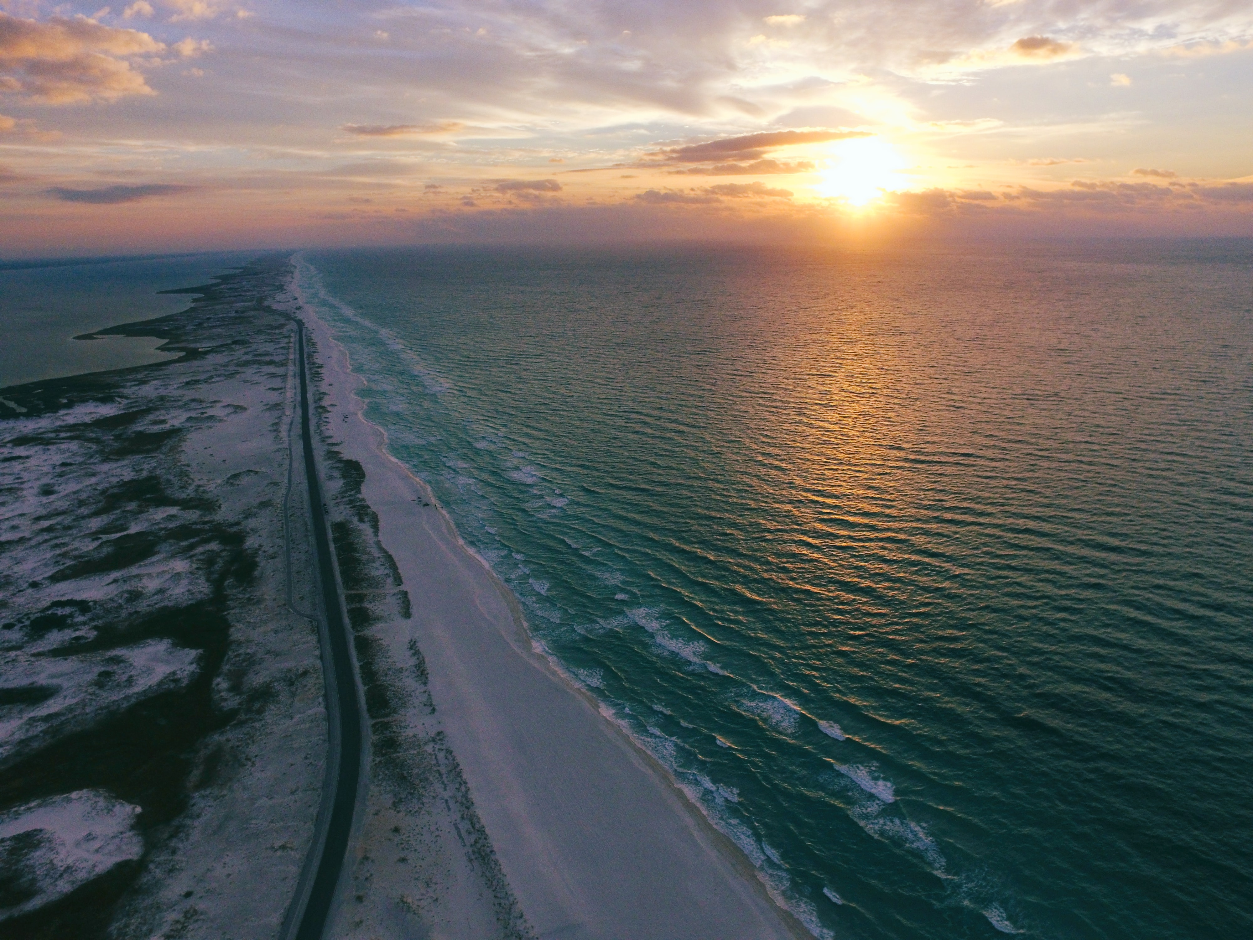 Drone view of an empty coastal road beside the beach, sun setting over rippling water