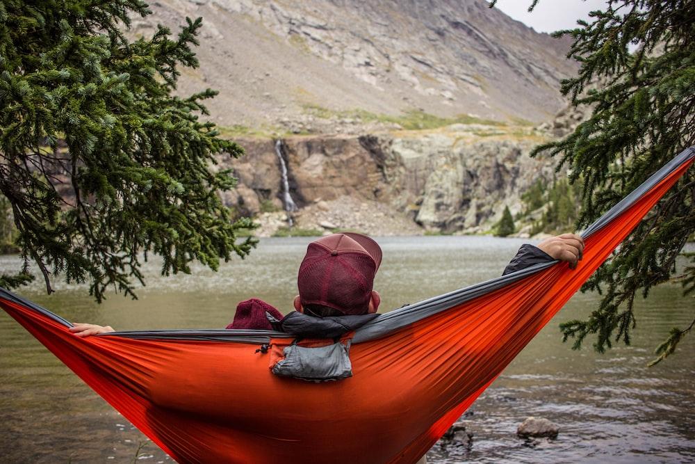 man lying on hammock beside trees