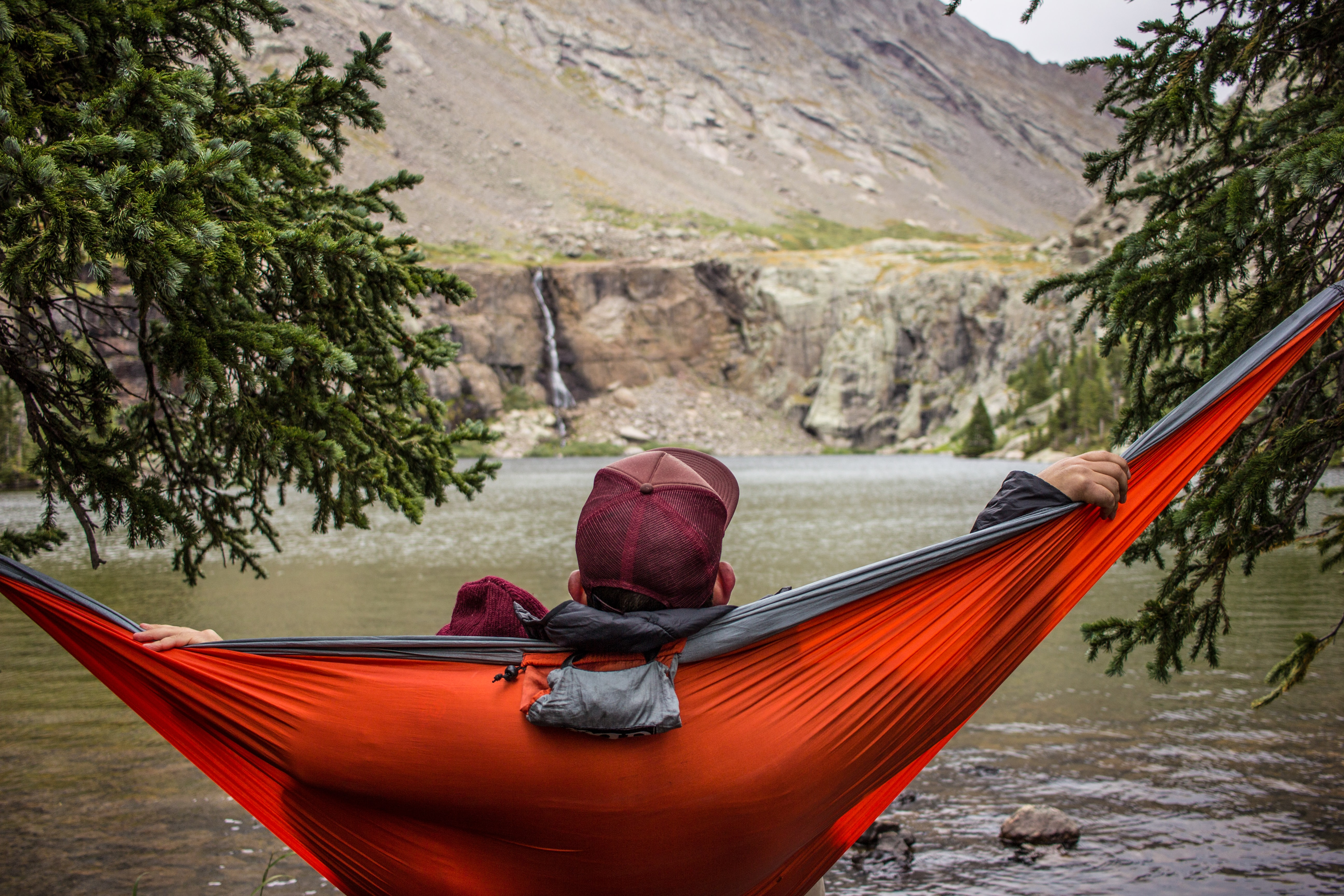 A man relaxes on a red hammock in the mountains by a lake