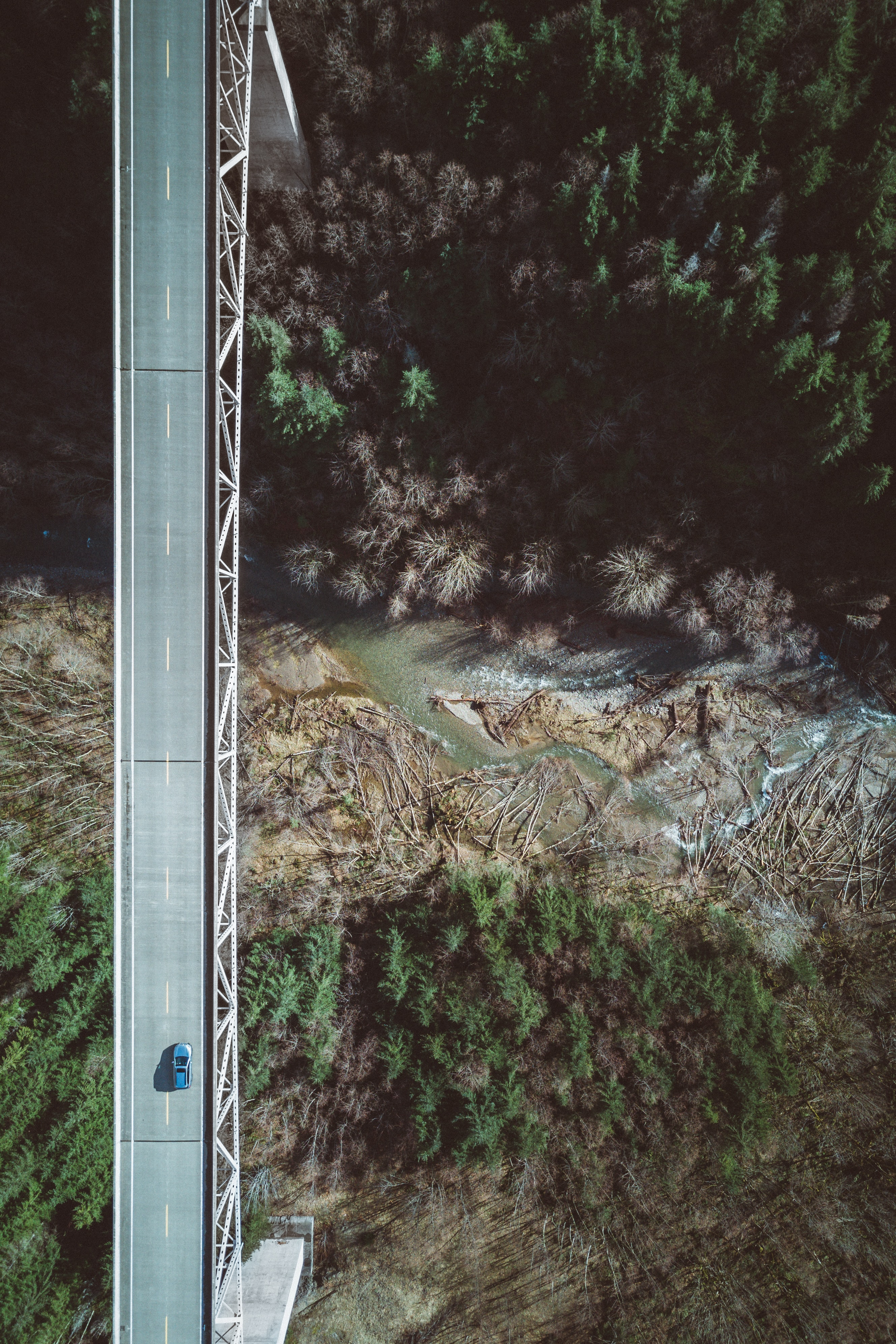 A drone shot of a car on a bridge over a deep ravine with a river