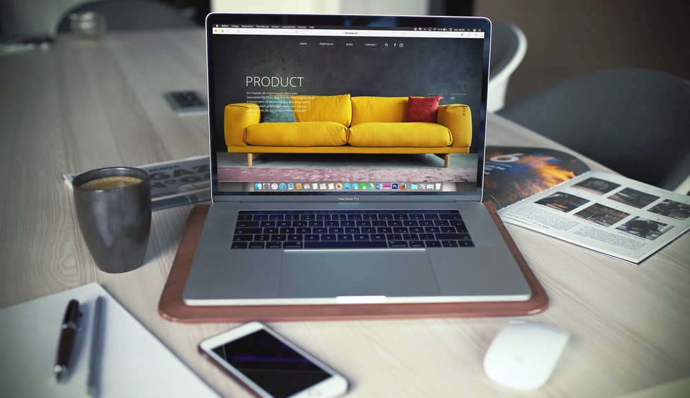 turned on MacBook Pro beside gray mug