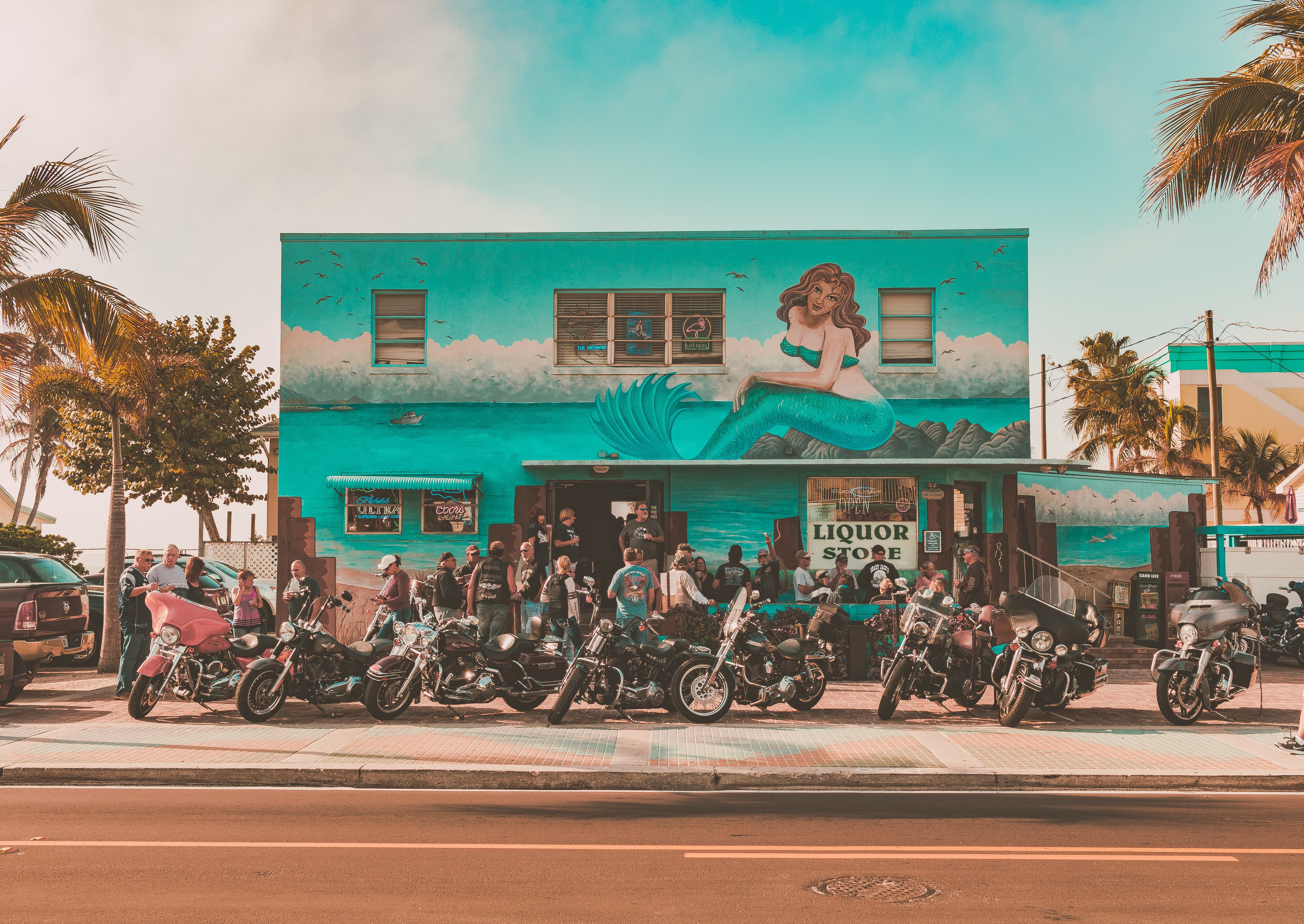 People and bikes in front of a liquor store with palm trees by its side