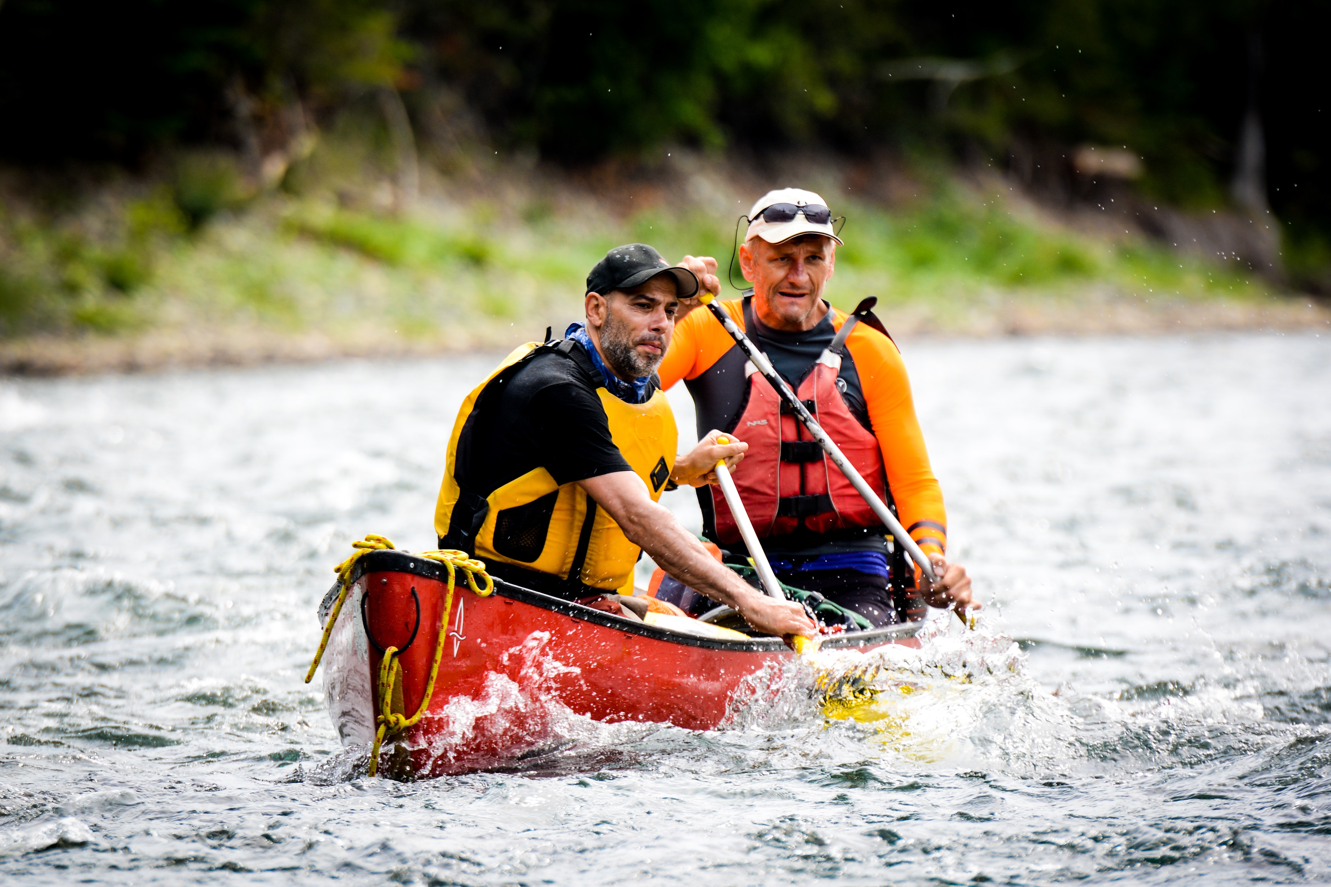 Two men wearing yellow life jackets paddling in a red canoe in the rapids