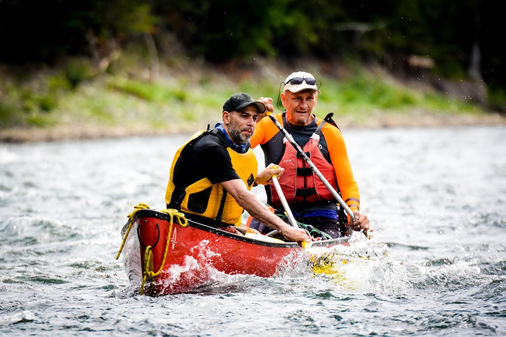 two men riding on red canoe boat