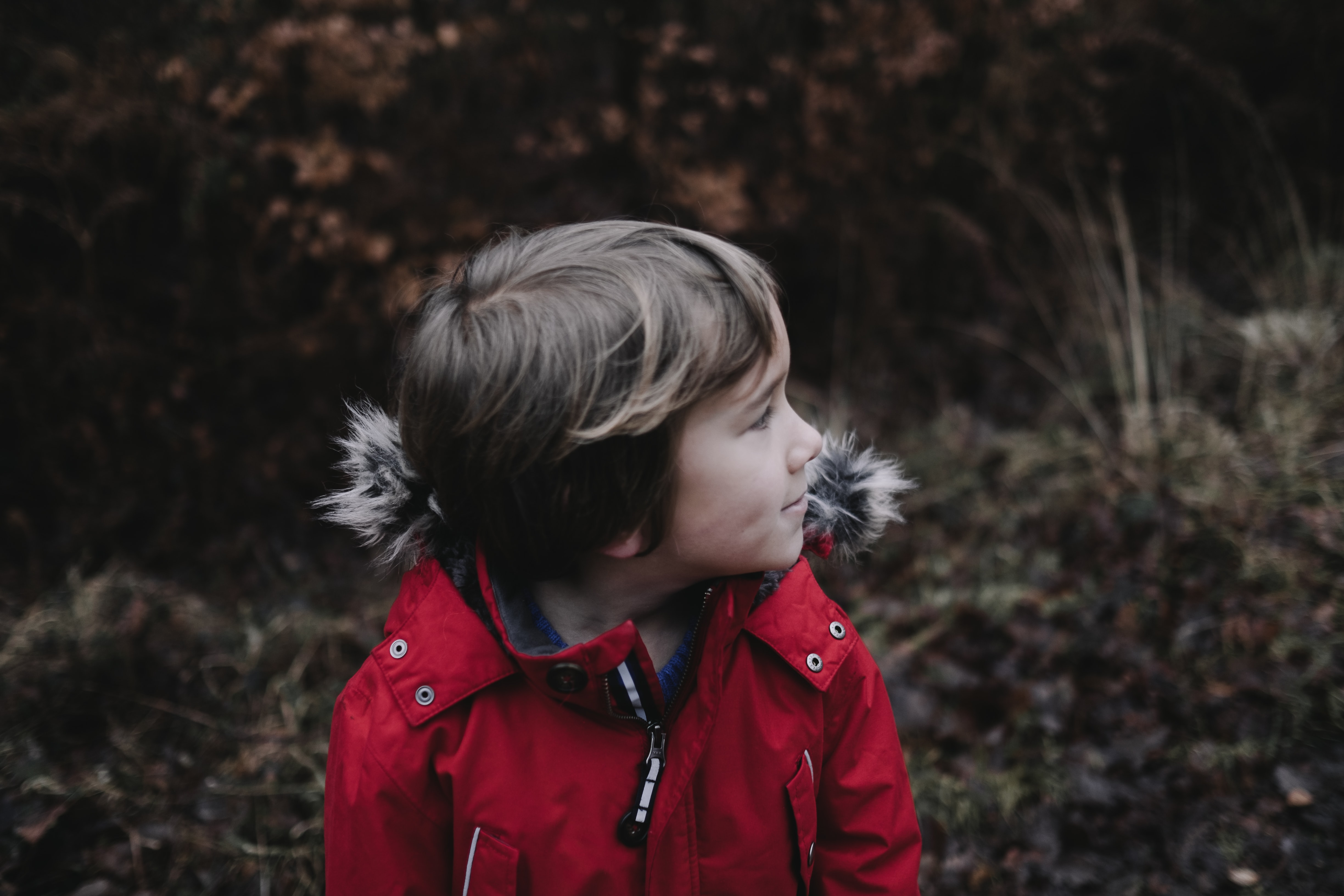 Happy young boy in a red winter coat outside
