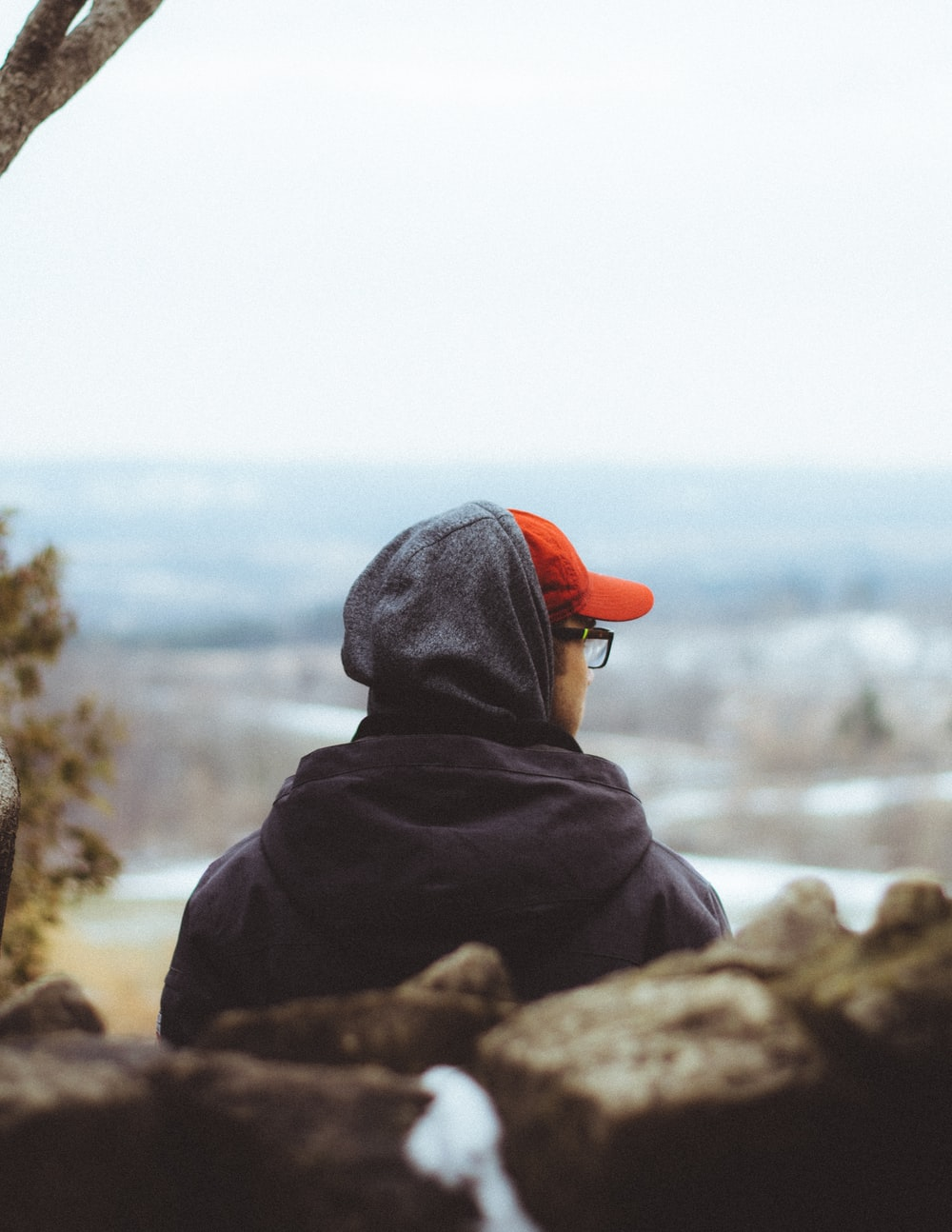 person in black hoodie and orange knit cap sitting on rock near body of water during
