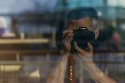 man holding dslr camera canon zoom background