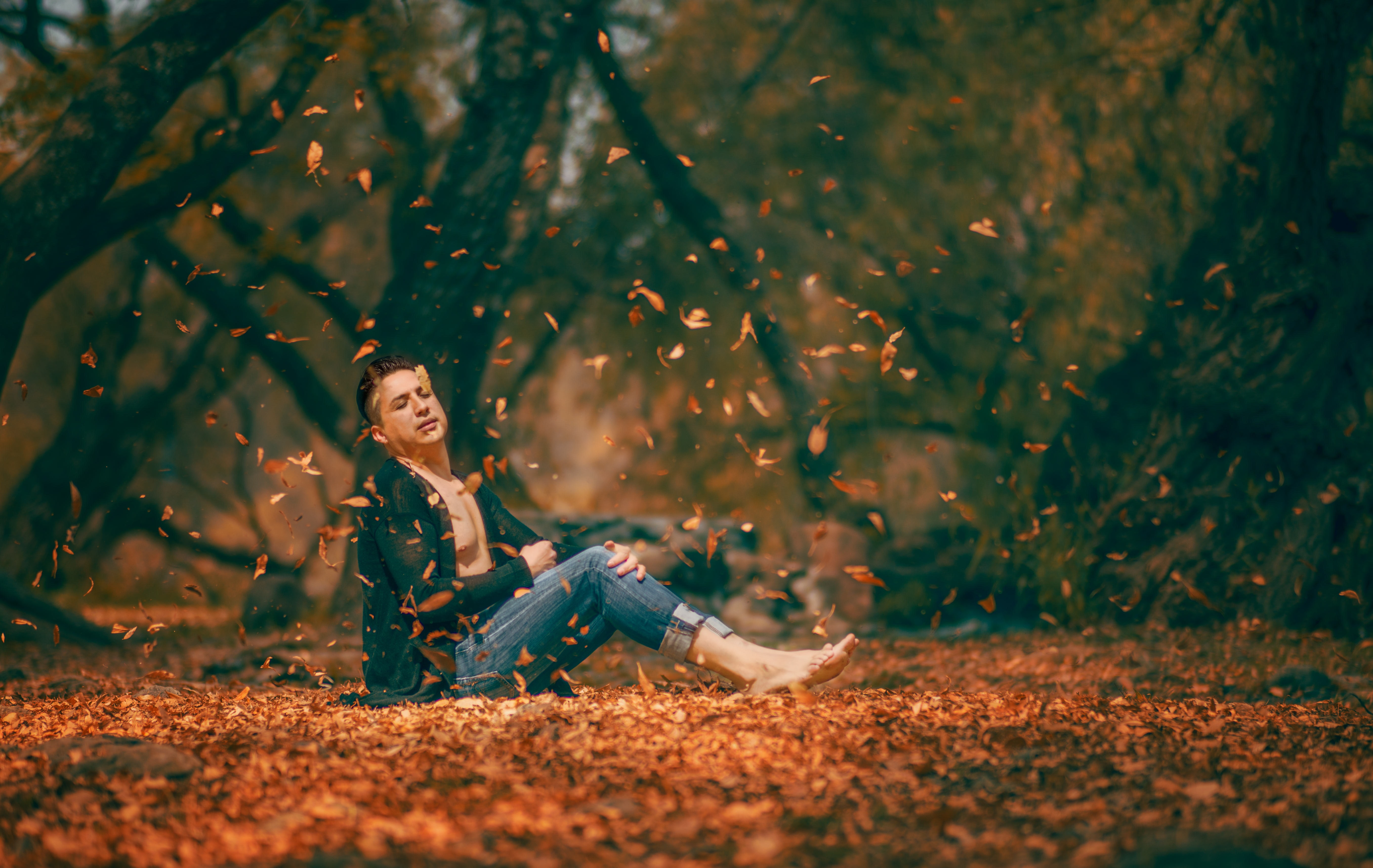 Shirtless man in a cardigan sits among falling fall leaves