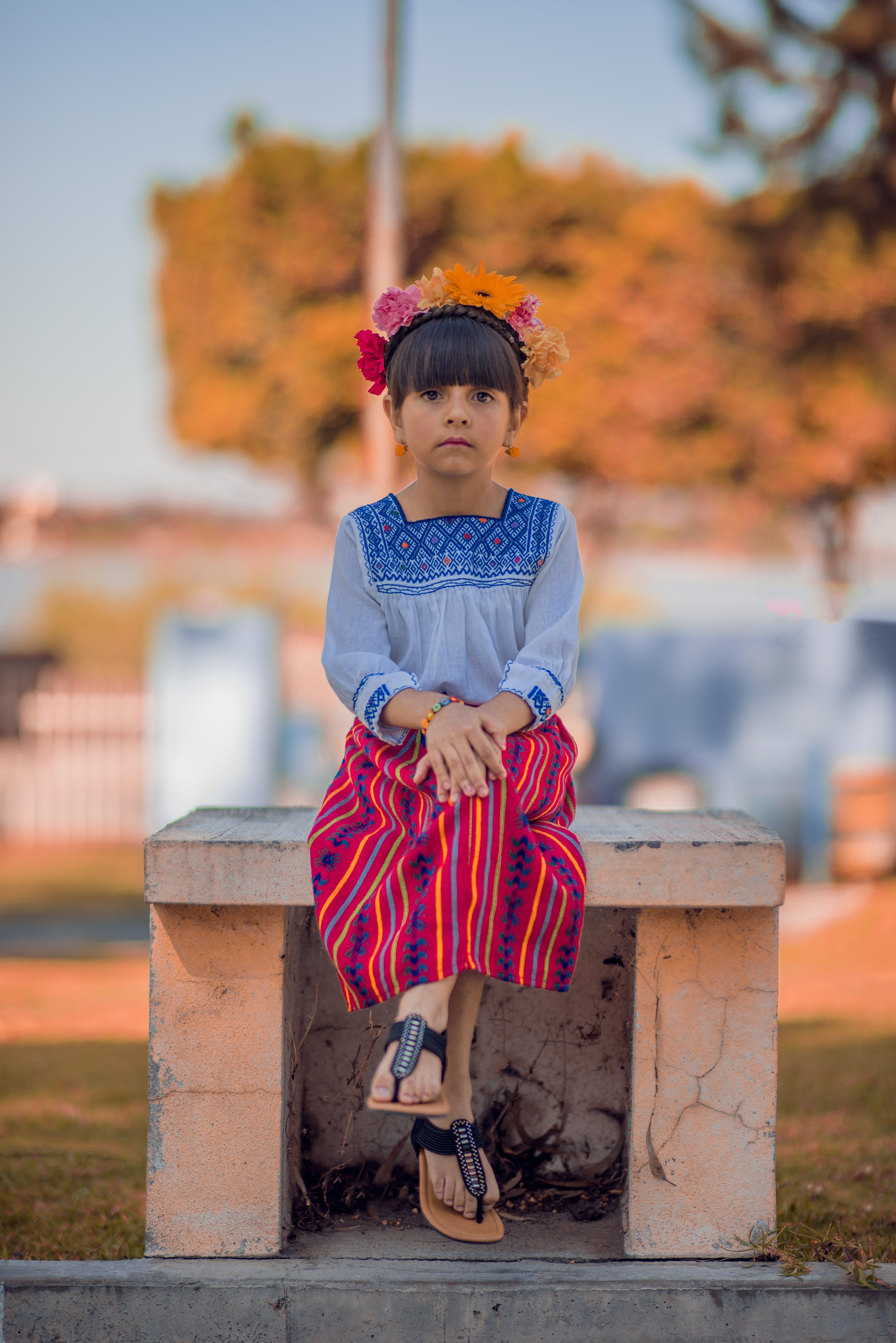 A little girl in a dress and a flower headband sitting on a concrete bench