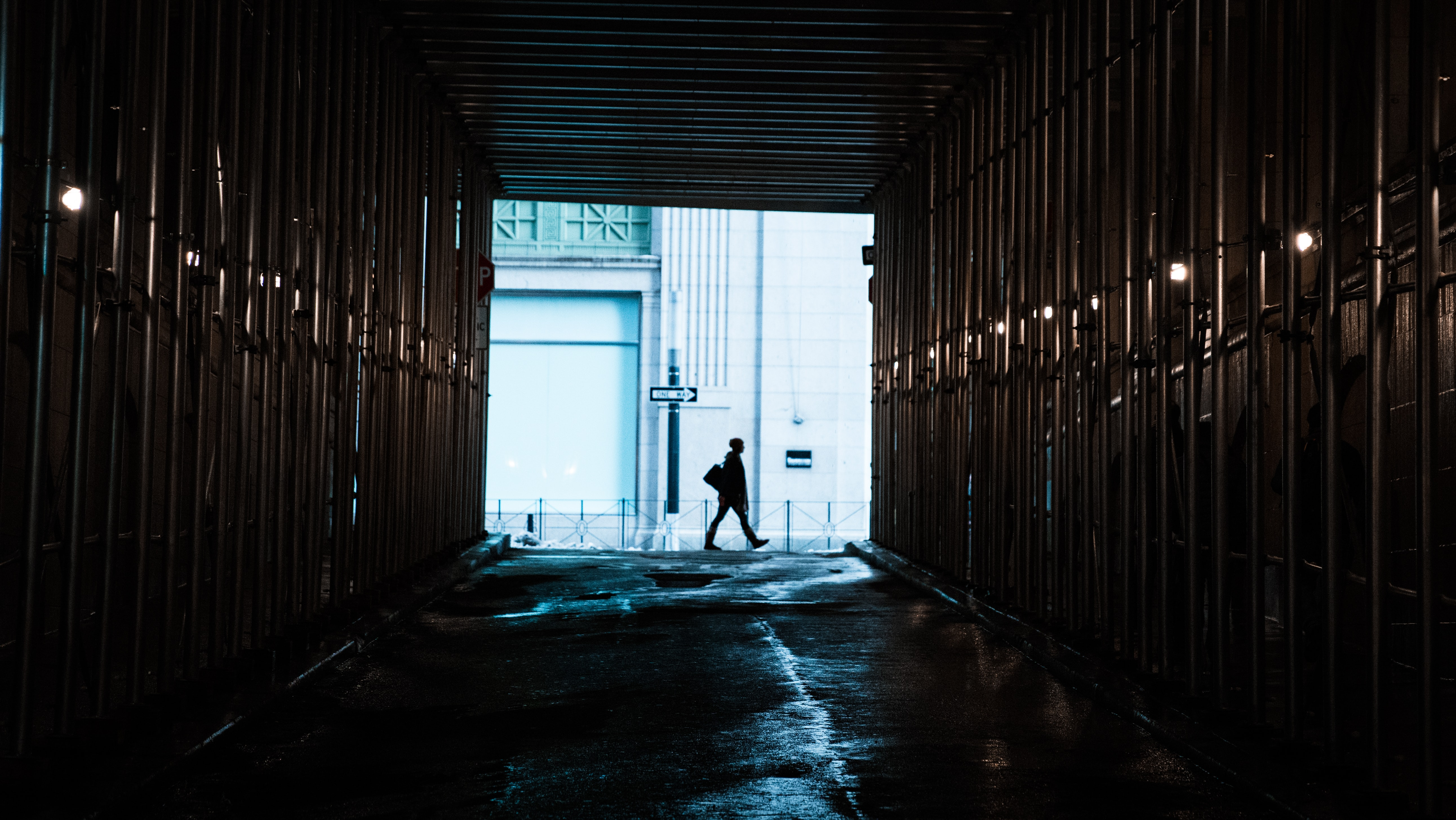 person walking in front of tunnel