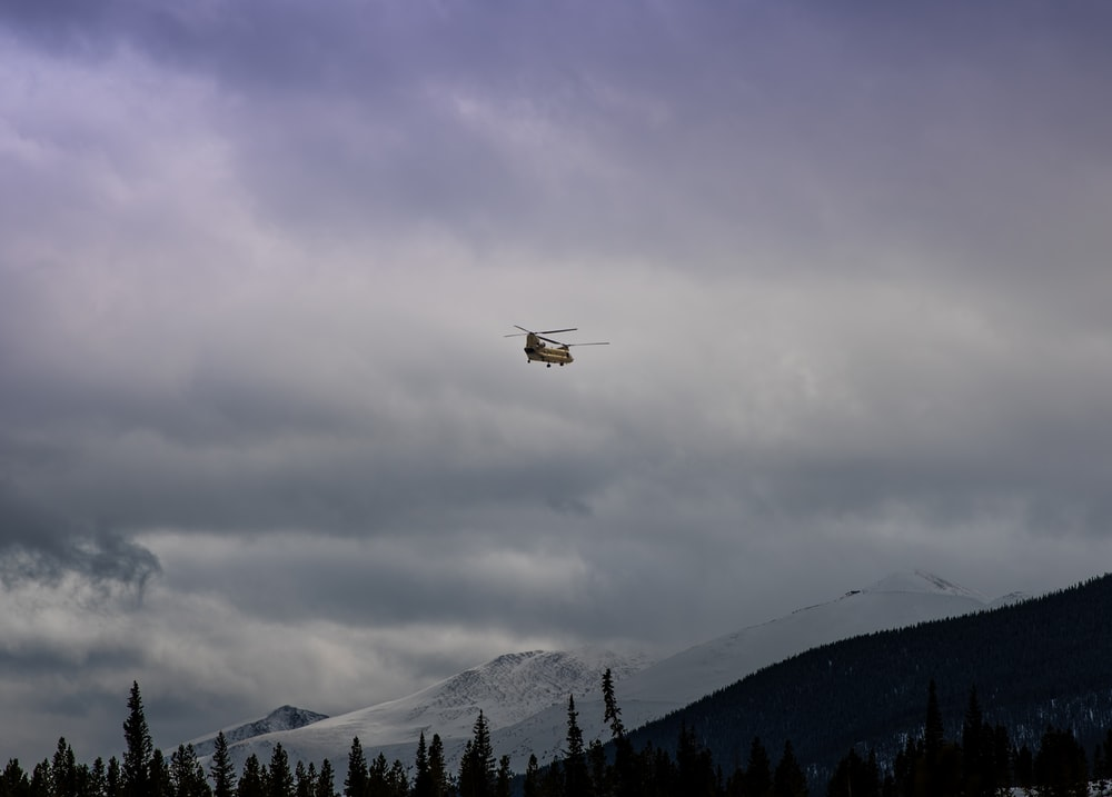 brown helicopter flying under cloudy sky