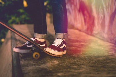 person standing beside skateboard skate zoom background