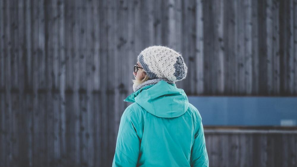 selective focus photography of woman facing wall