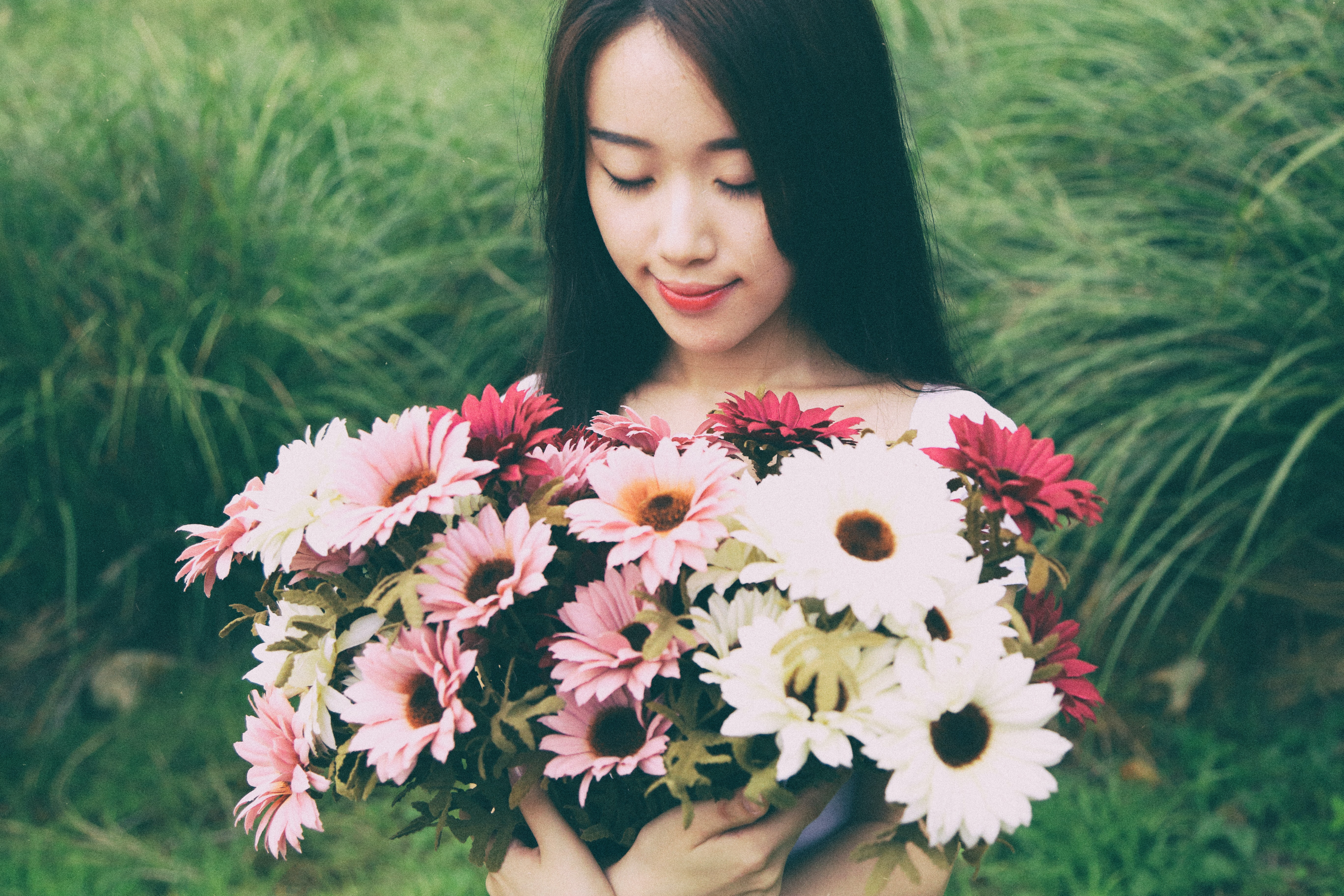 A dark-haired woman holding a large bouquet of pink and white flowers in a meadow