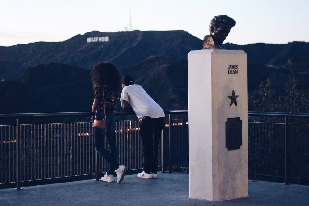 two man and woman leaning on railing and Hollywood Sign at the distance during day