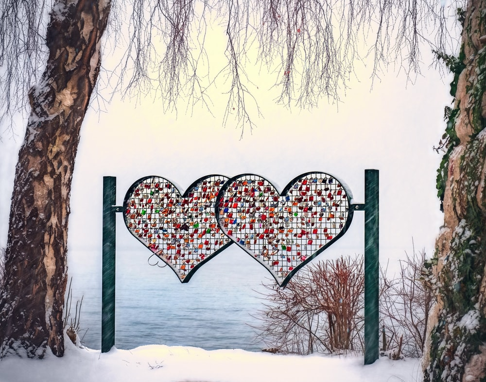Two colorful heart shapes hanging from poles in front of the water.