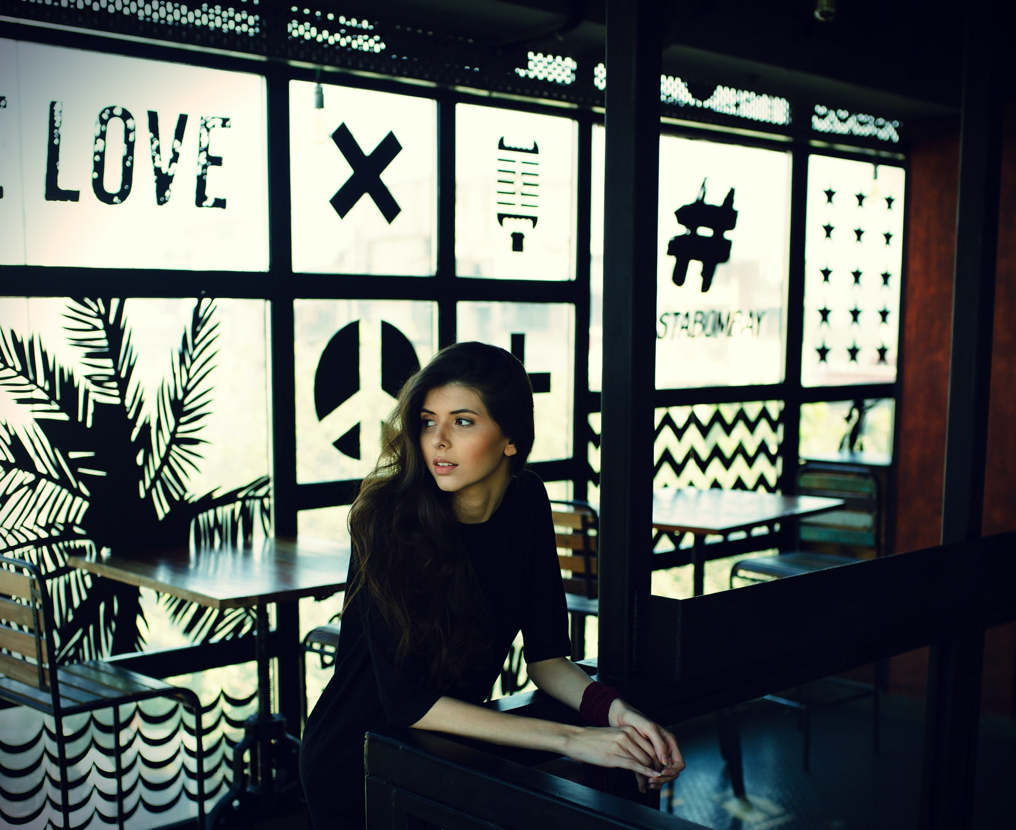 A young woman sits at a table in a cafe with decorated frosted windows