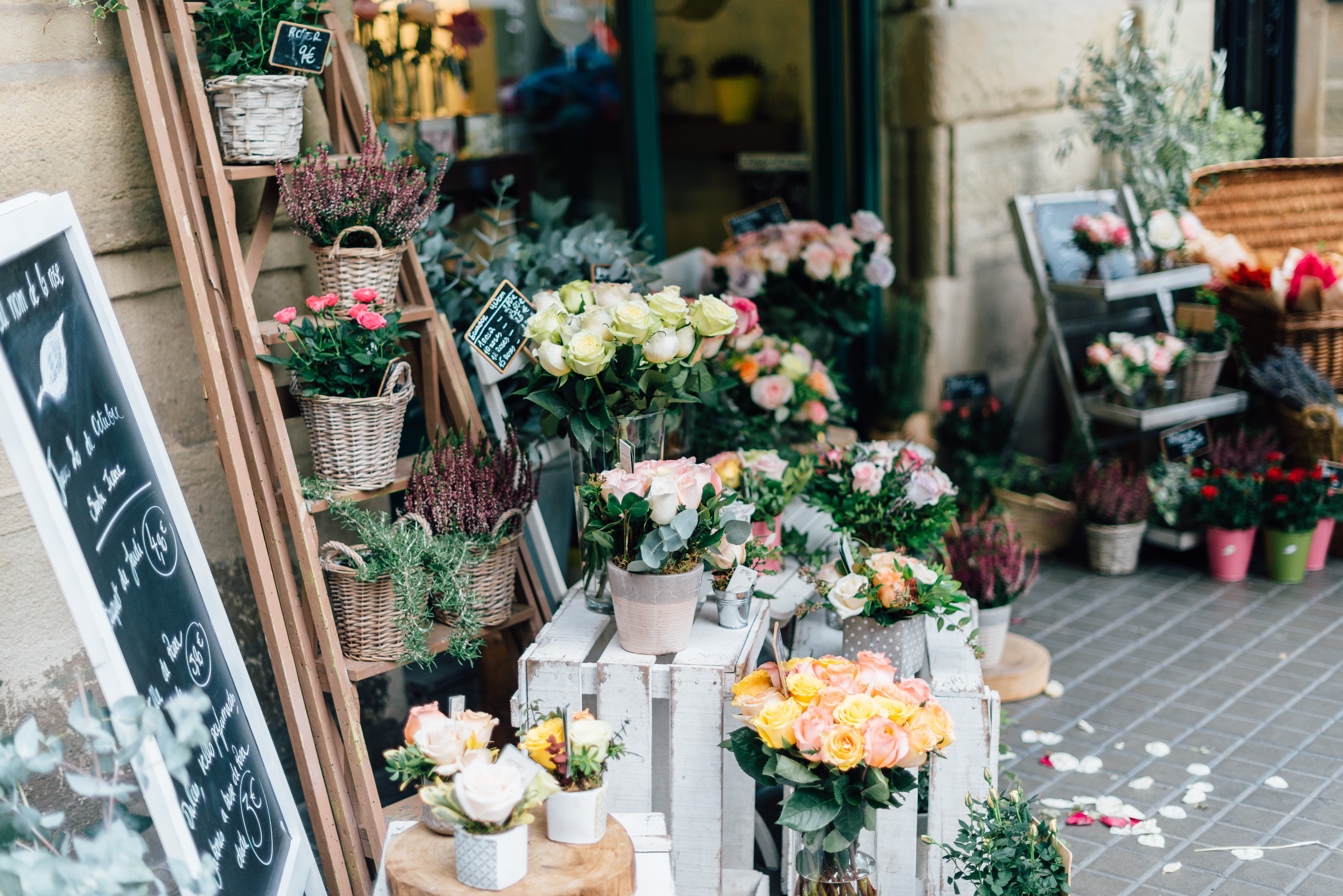 Pots and vases with various types of flowers at the entrance to the florist's