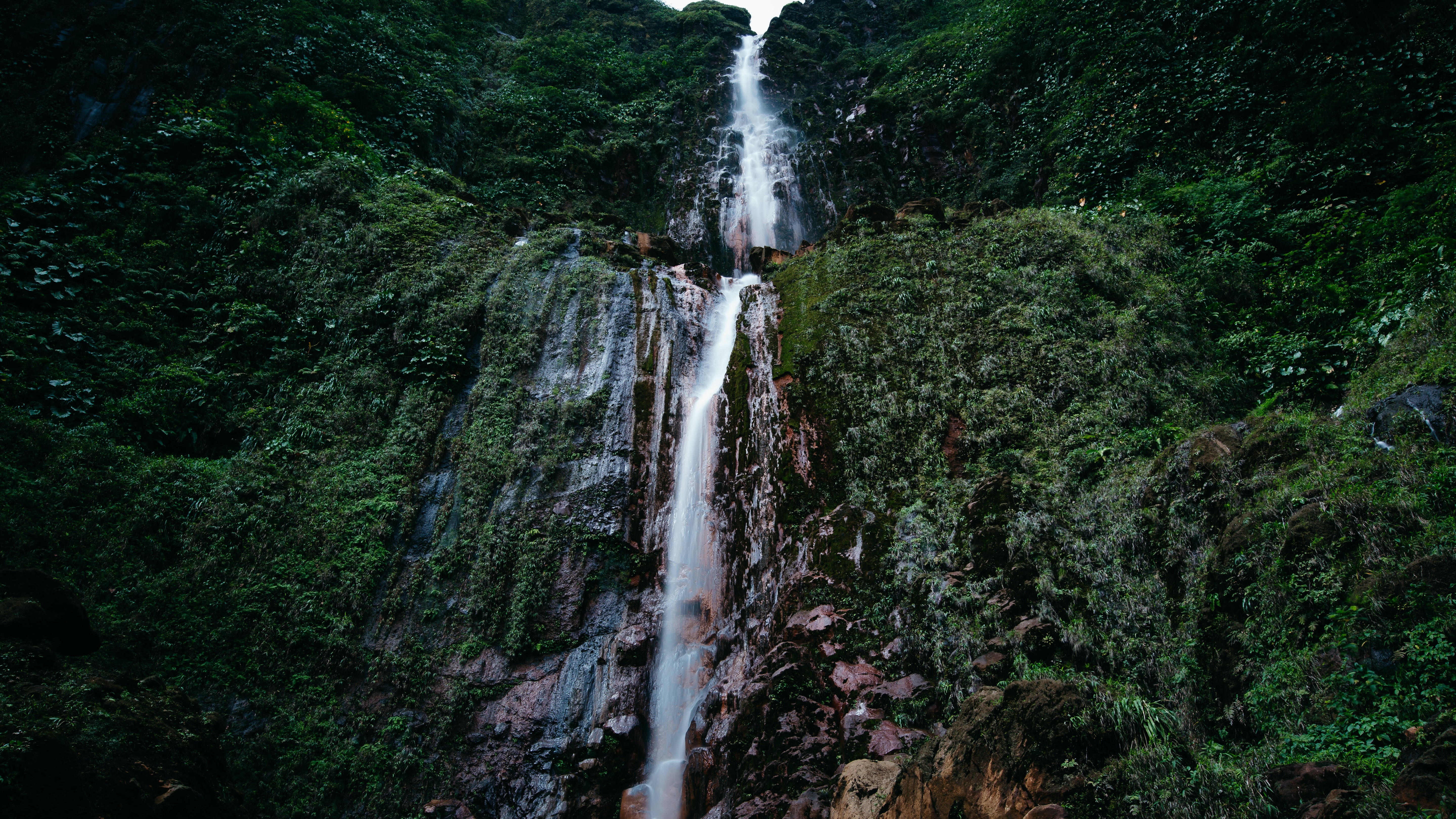 A tall waterfall flowing down a tall rock face covered in green vegetation