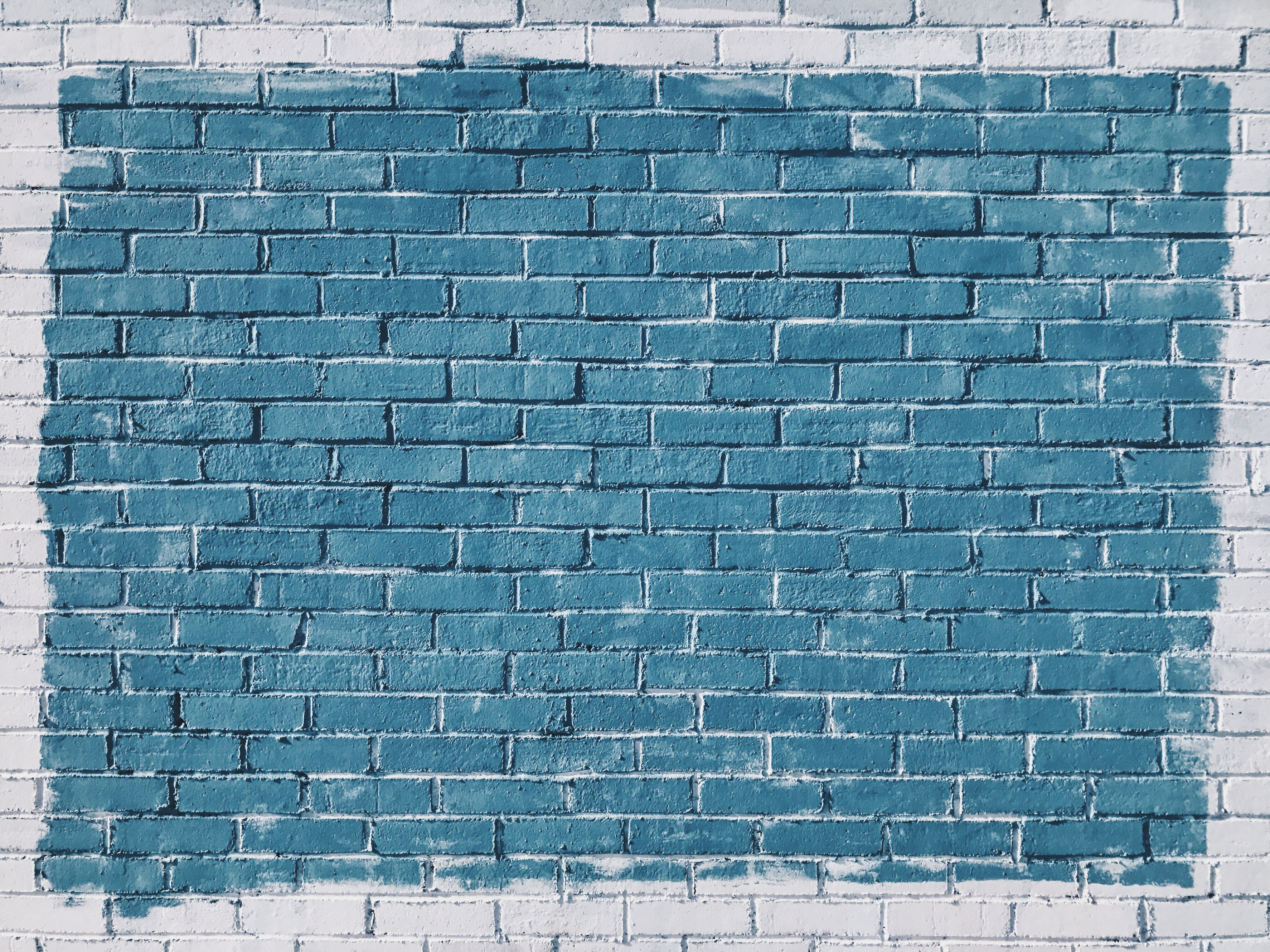 Blue painted rectangle on painted white brick wall