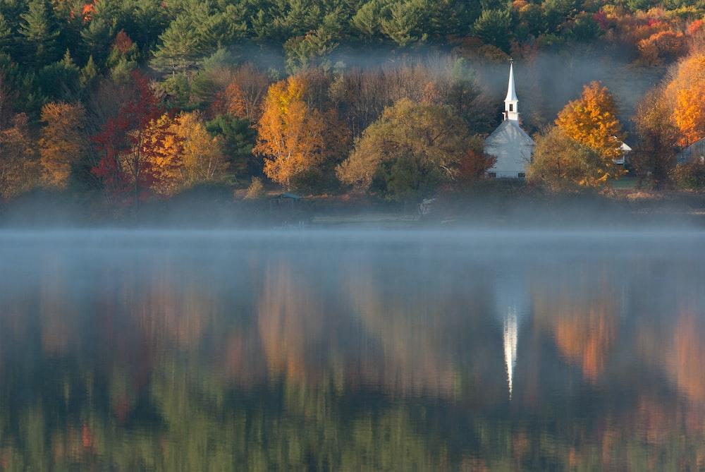 white chapel beside body of water
