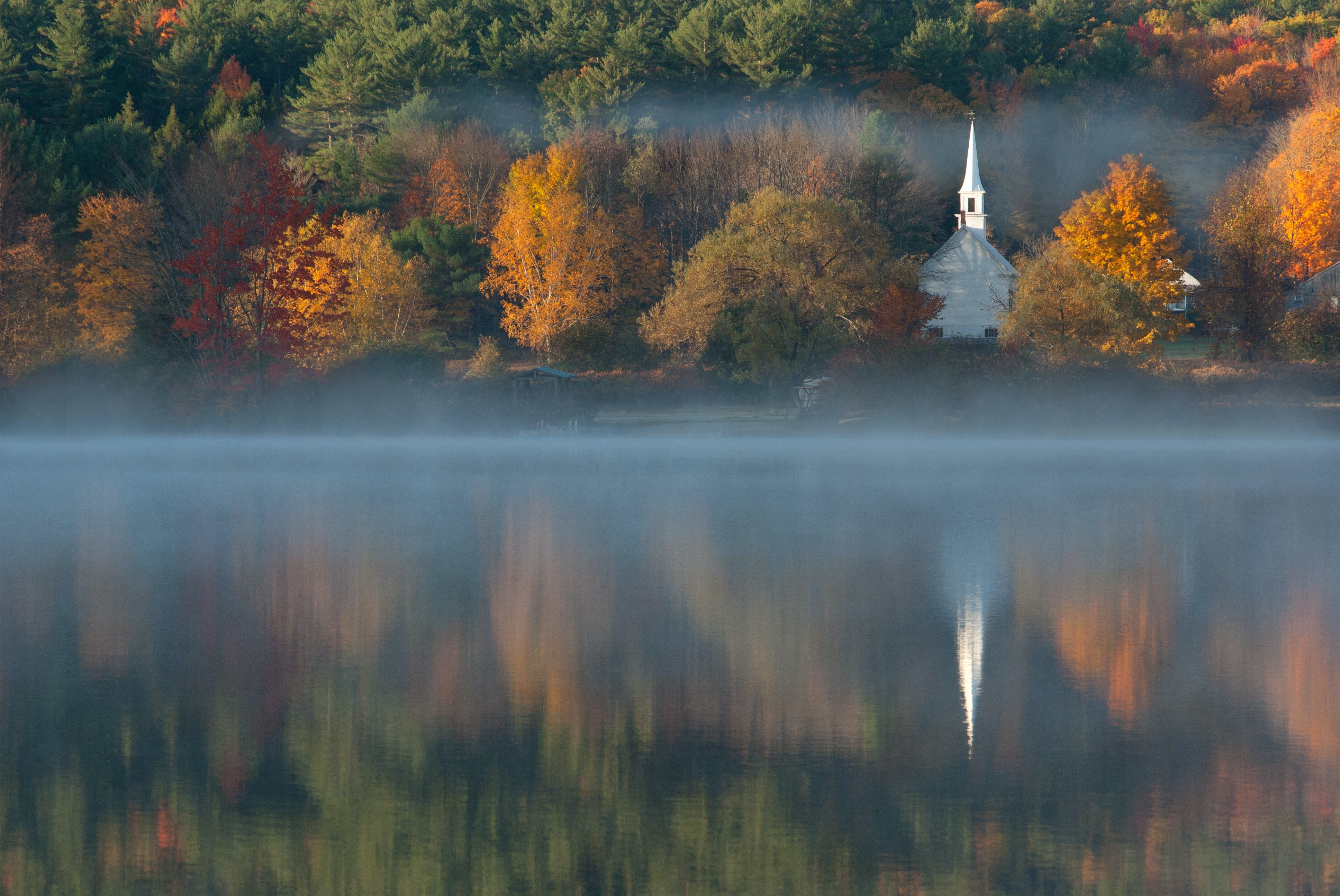 A scenic view of a small church on the shore of a hazy lake in Eaton