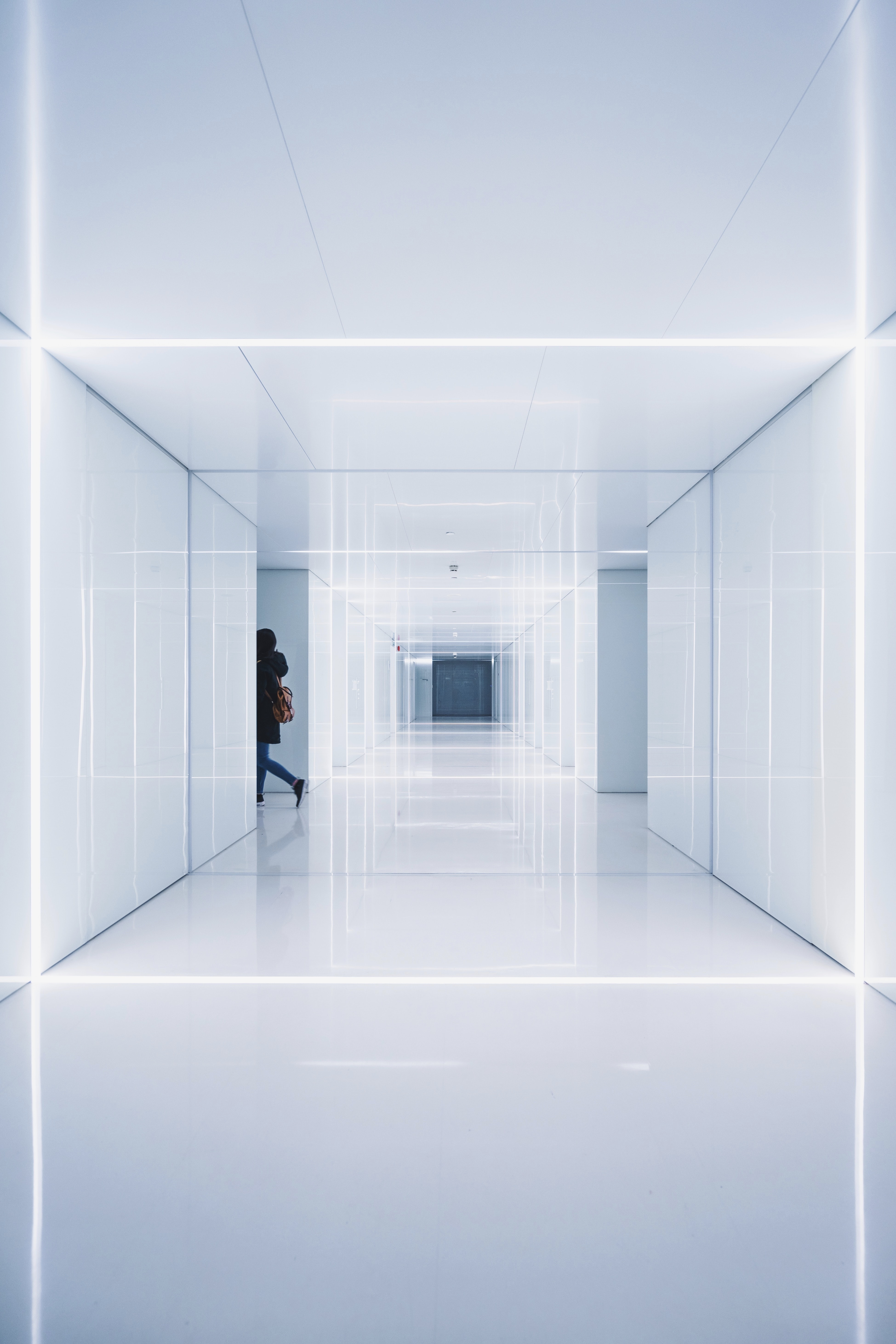 A woman disappearing behind a corner in a glossy white corridor