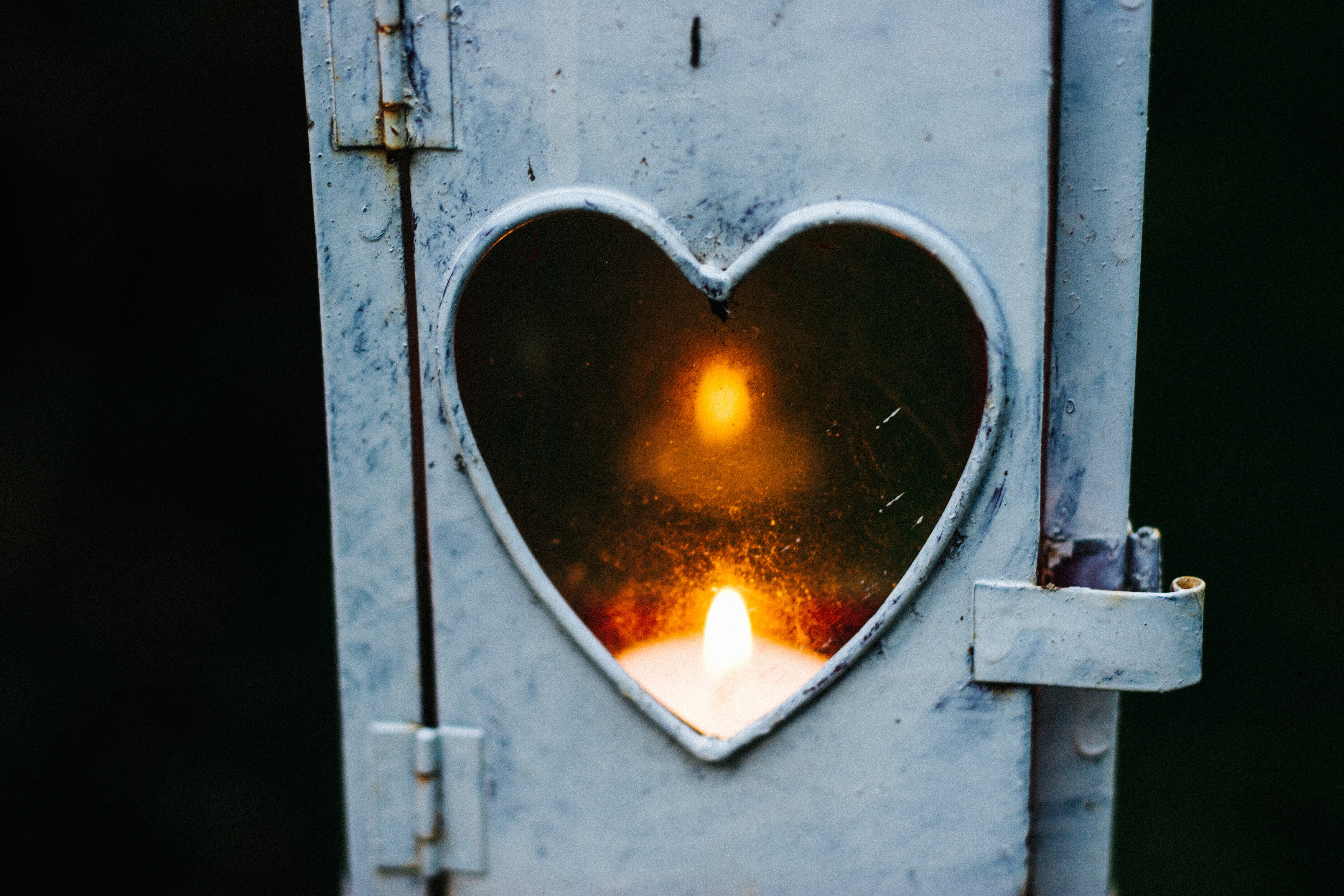 Funky metal lantern with a heart-shaped window illuminated by candle