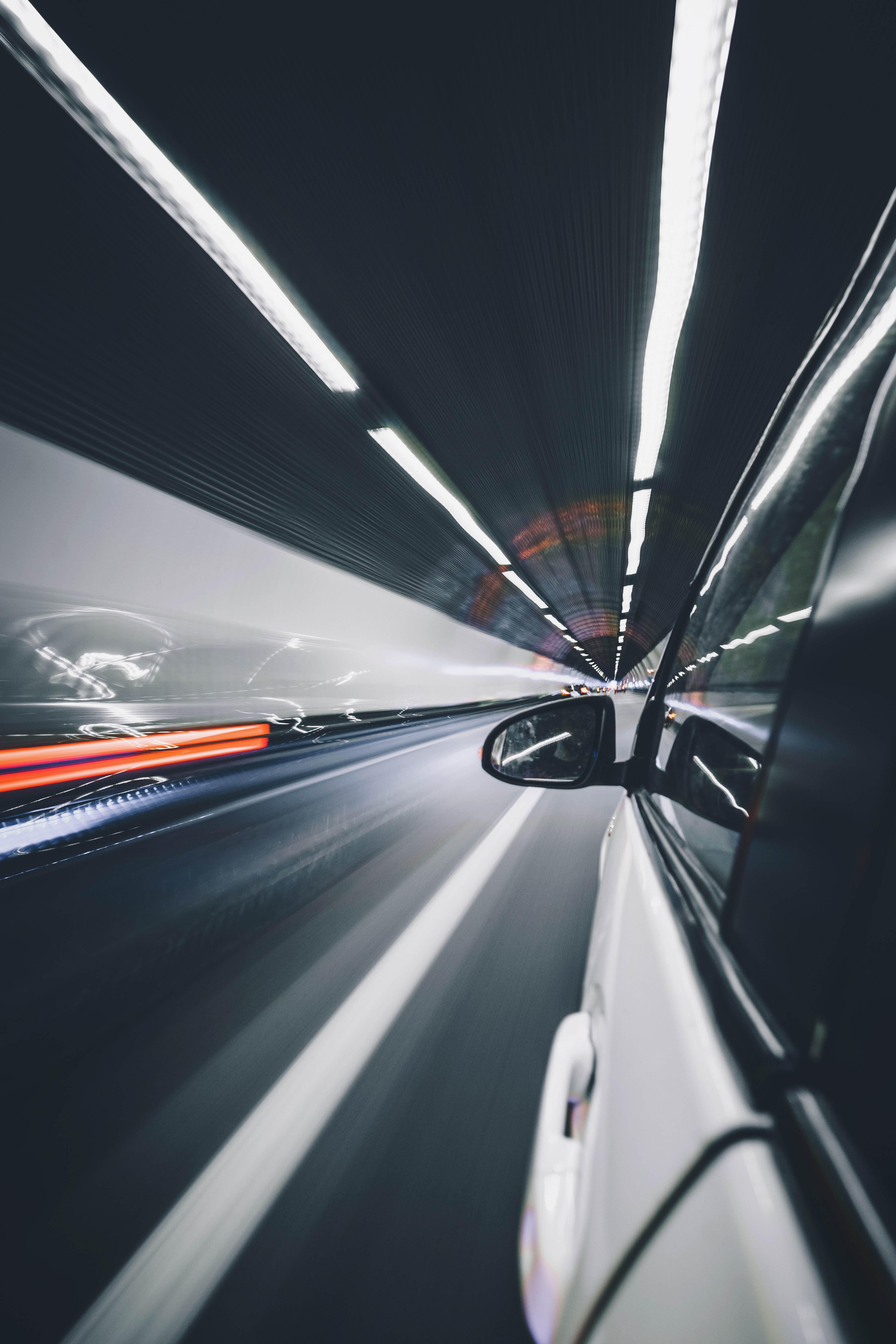 Long exposure photo of a white car driving through a tunnel with traffic lights