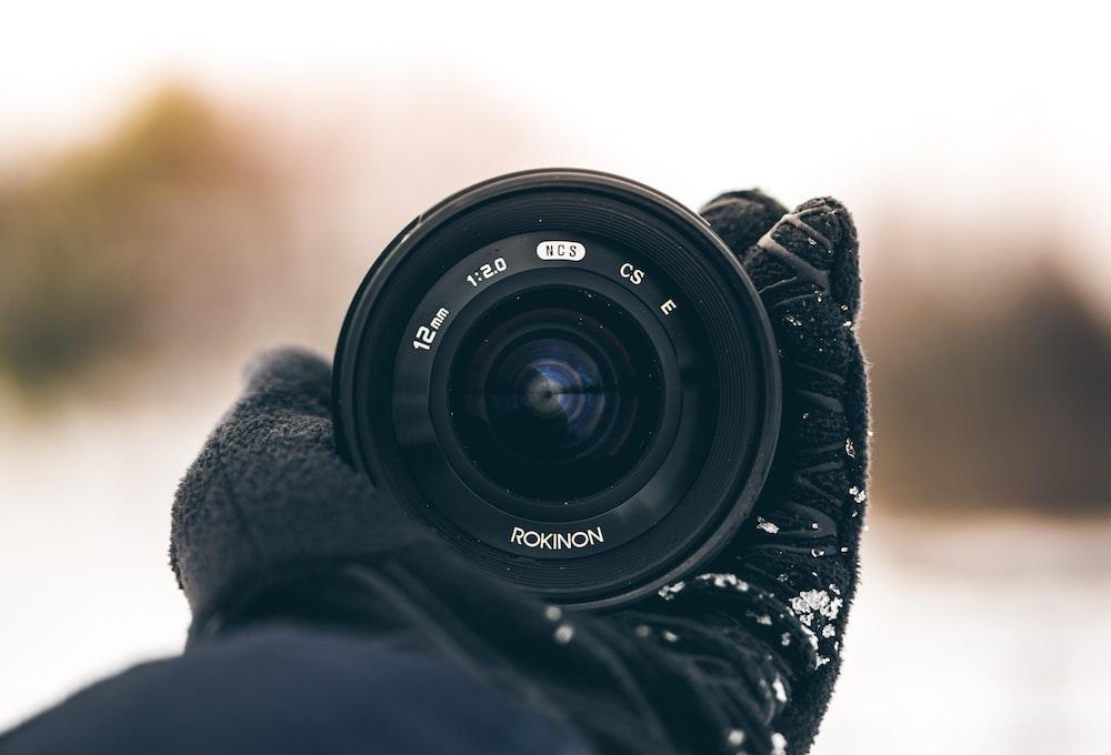 person holding Rokinon zoom lens