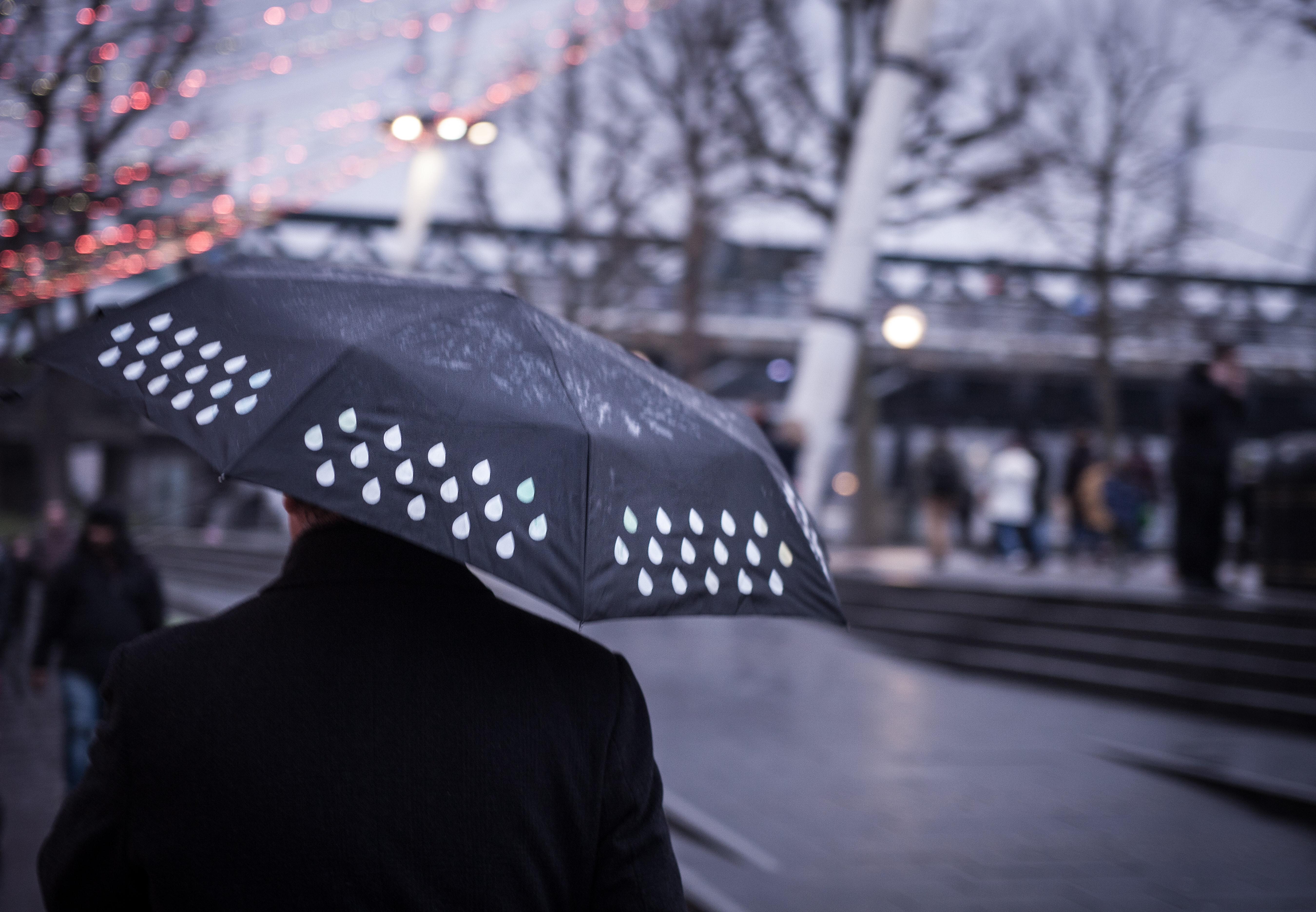 A blurry shot of a man with a wet black umbrella in London