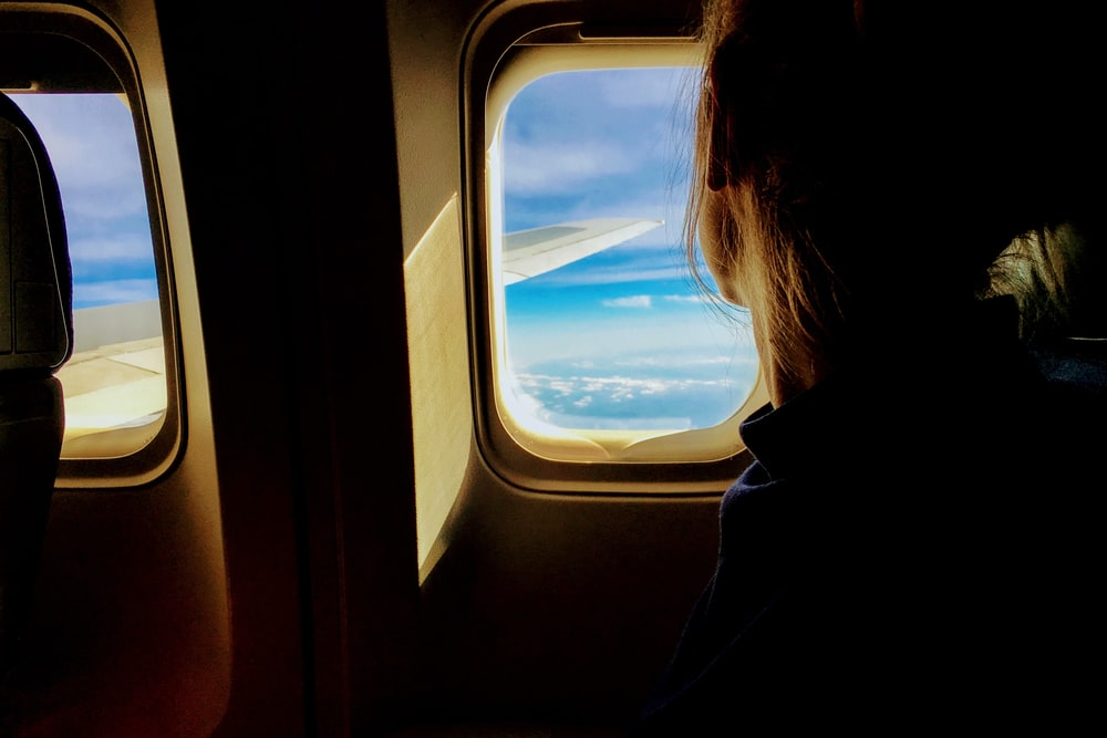 A woman looking out an airplane window with a view on the wing and scattered clouds