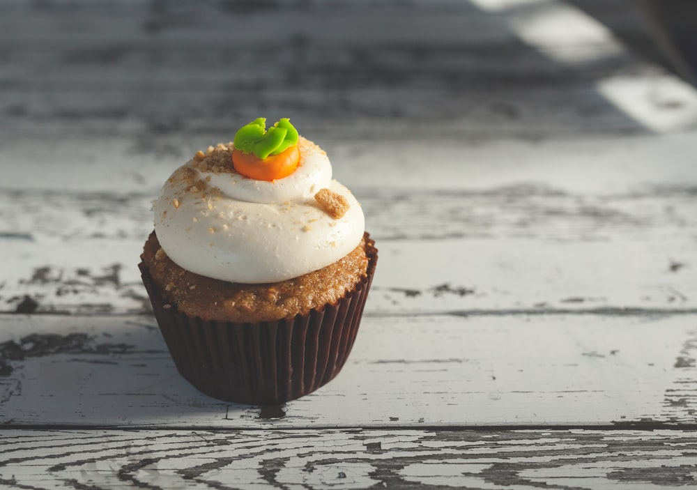Single carrot cake cupcake topped with frosting