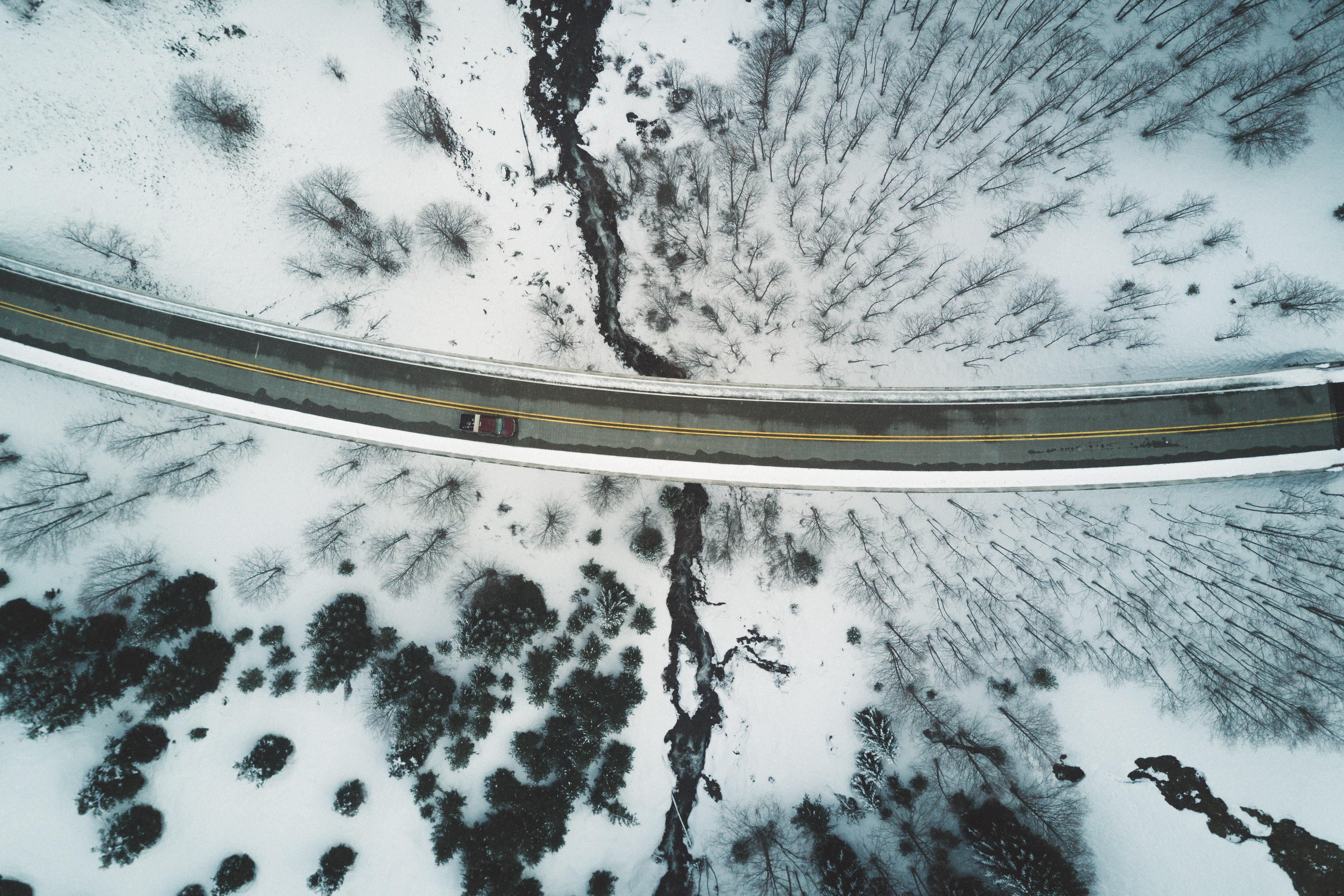 Drone shot of a car driving along a bend in a road in the winter