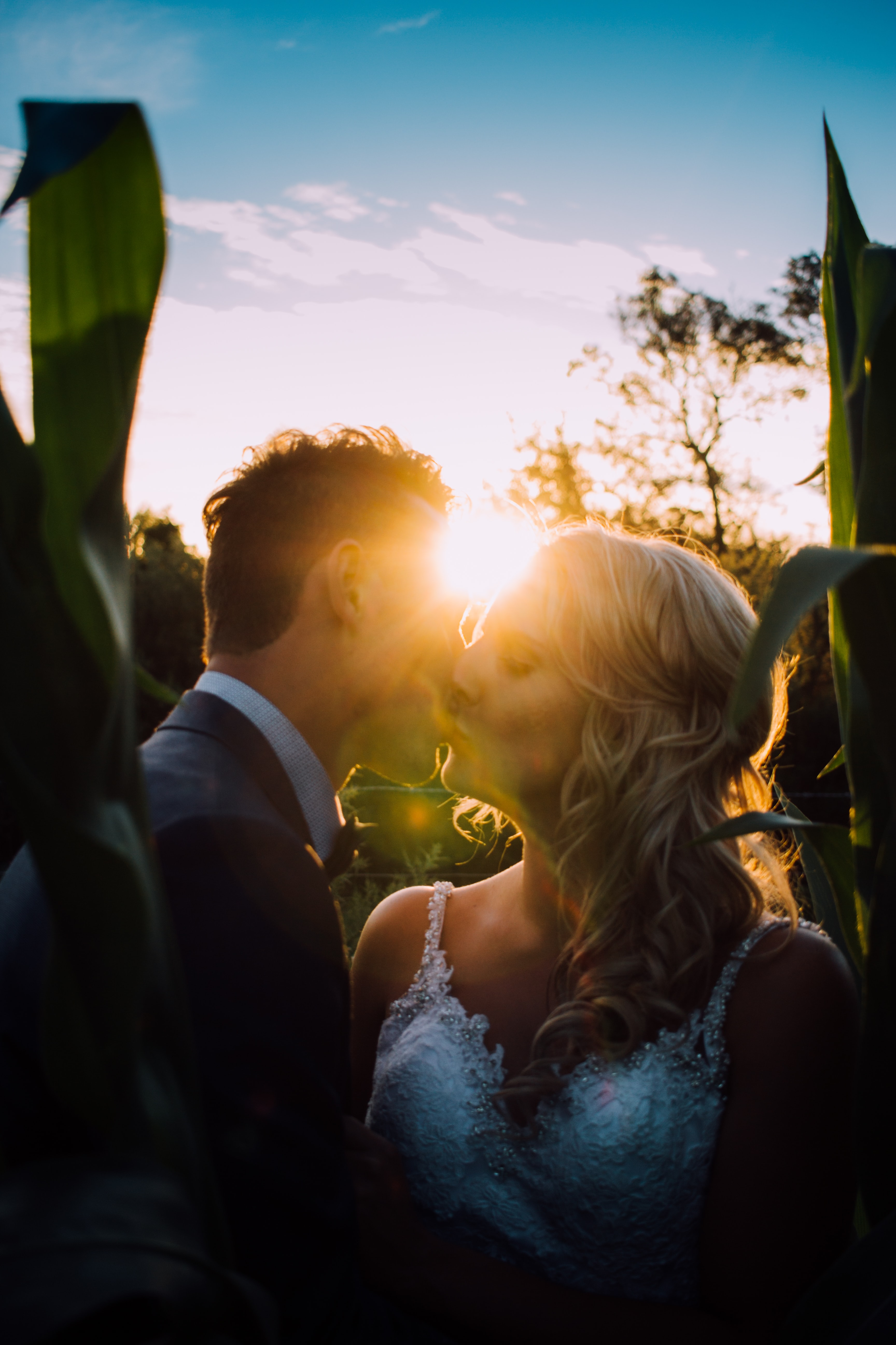 A bride and groom kiss each other at their wedding, the sun shining brightly in the background