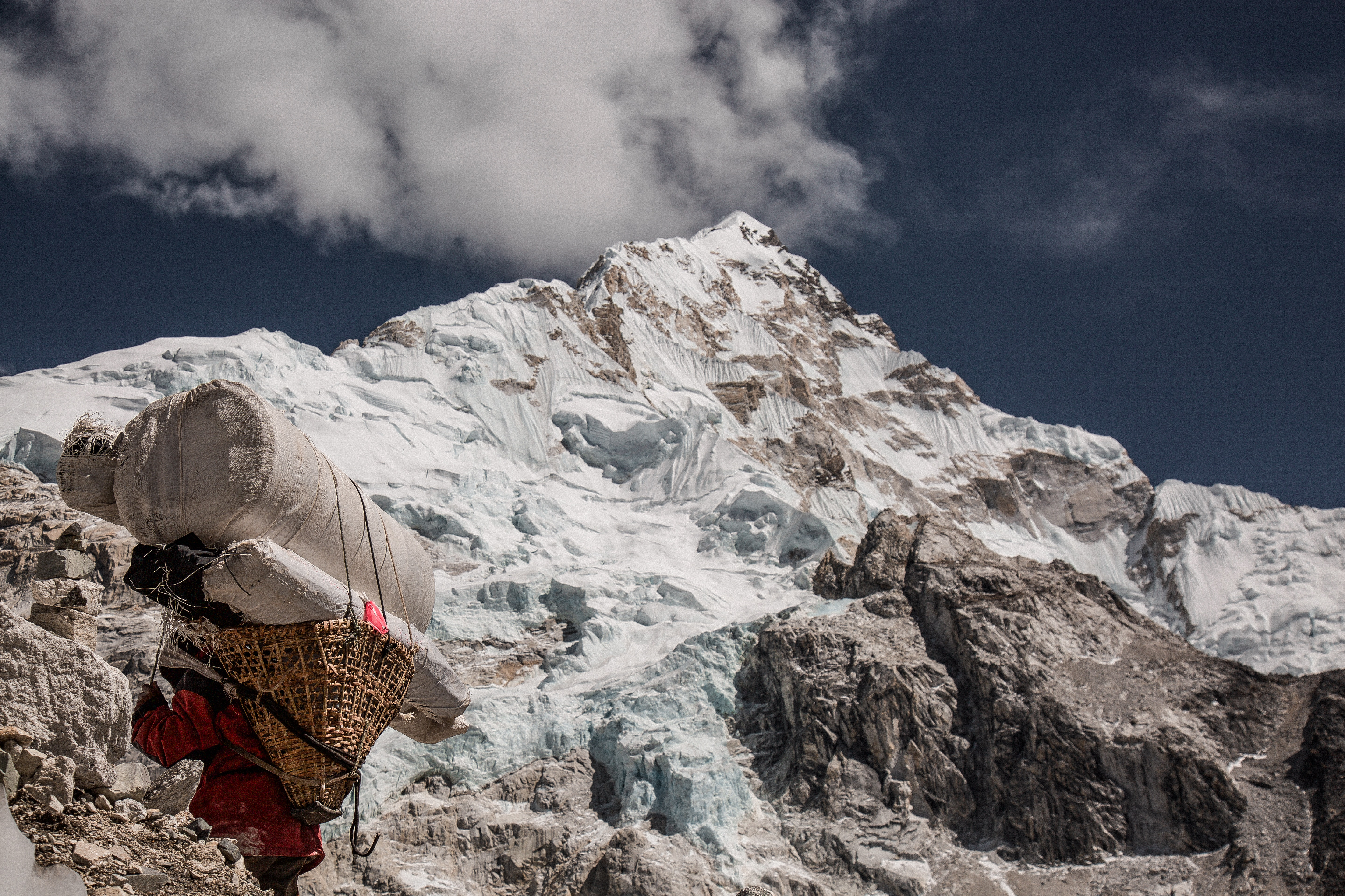 A climber carrying a basket with load, trekking on snow in Nepal