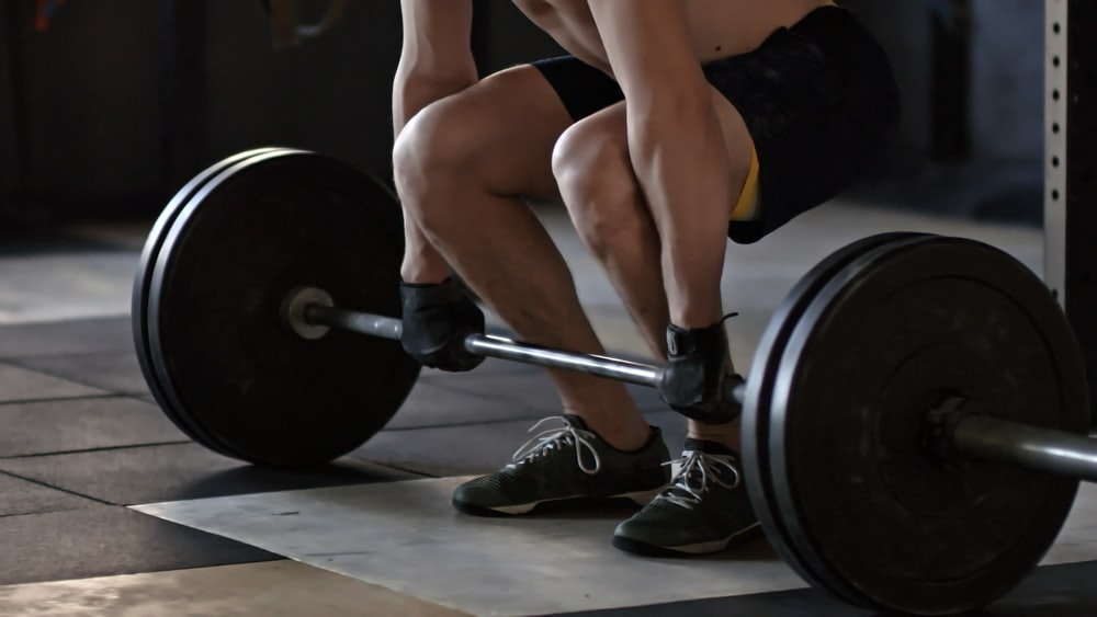 A person bending over to lift a barbell with two 45 pound plates on each side.