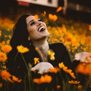 woman laughing on flower field