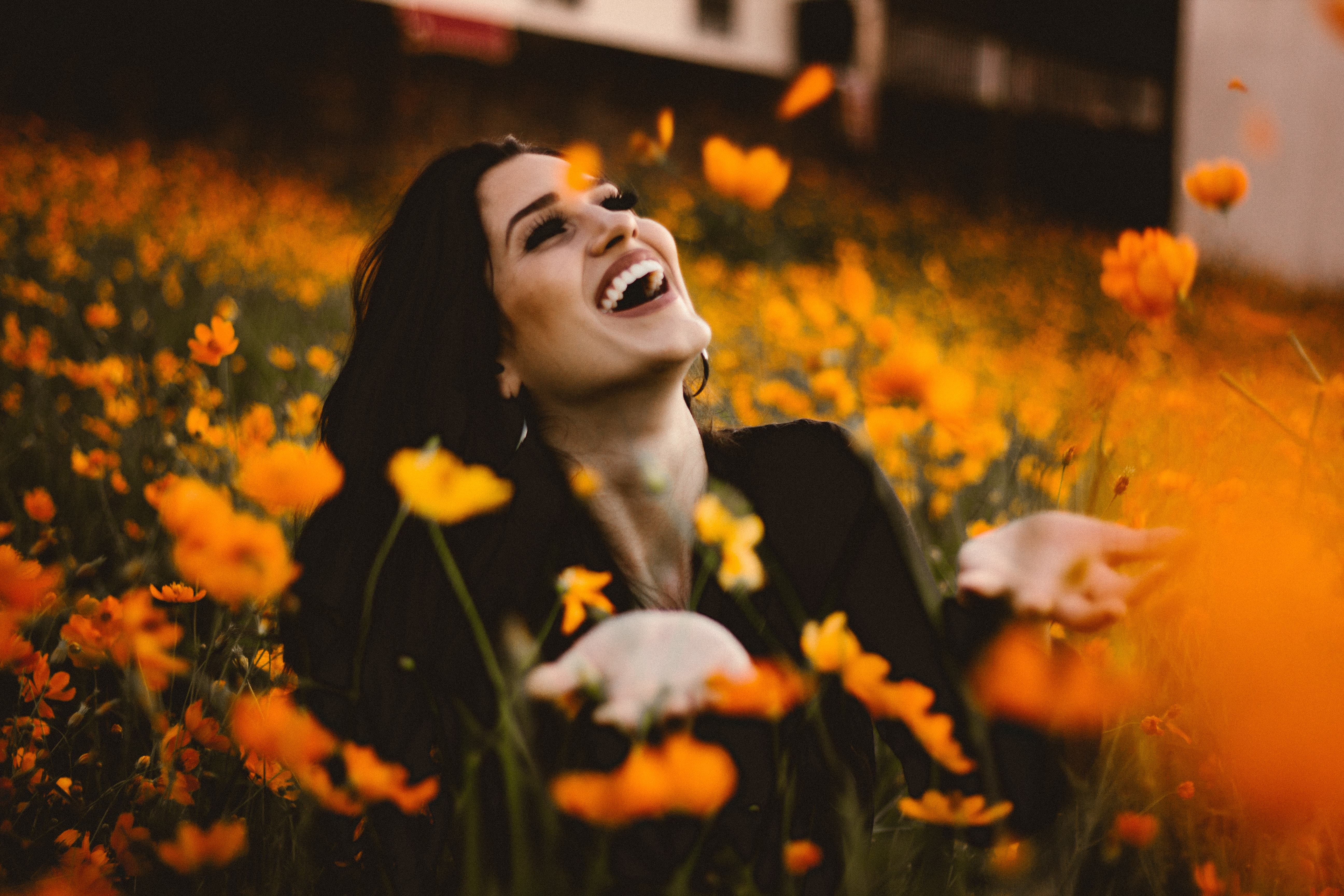 A woman wearing a huge smile while sitting in a field of orange flowers.
