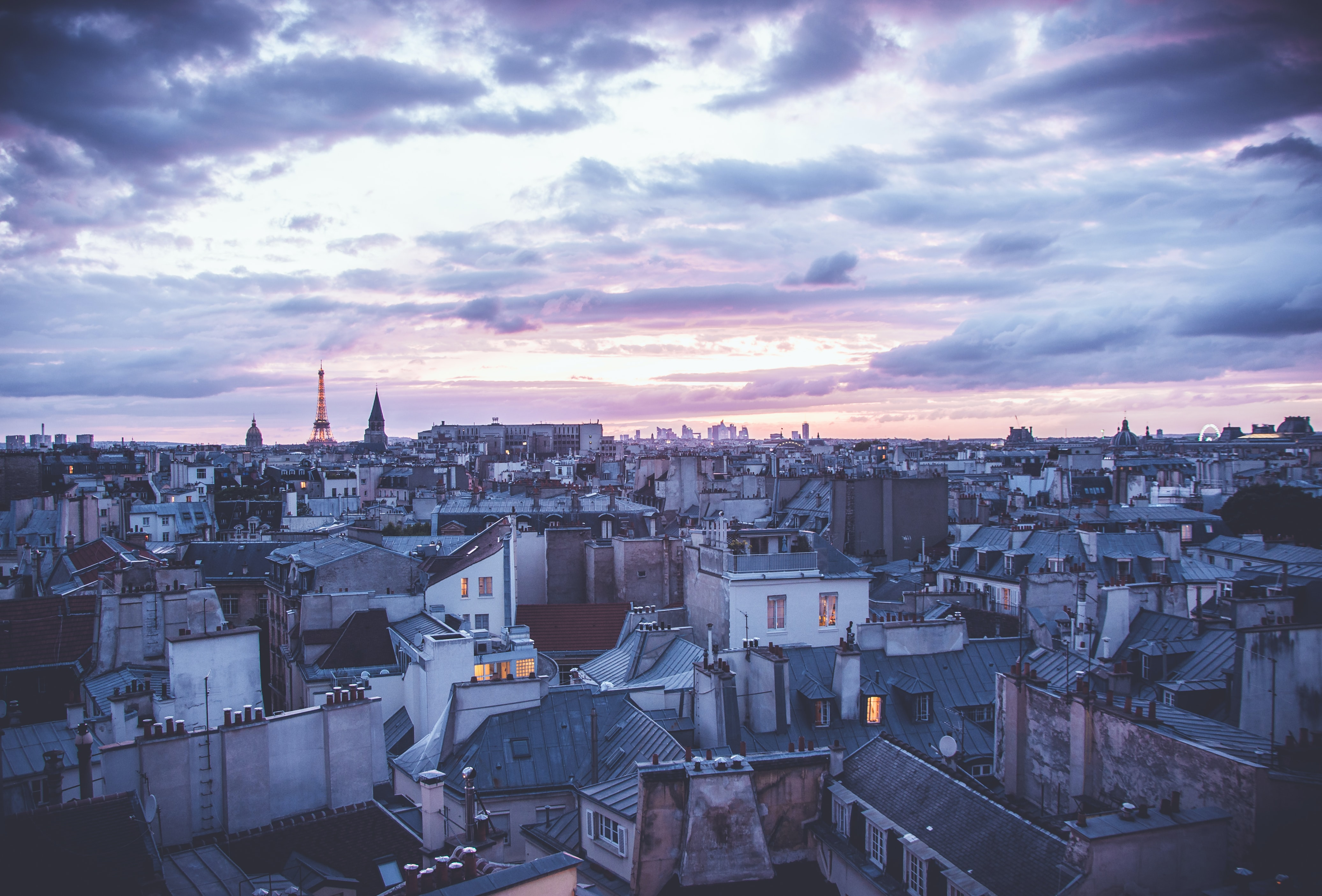 A view of the urban cityscape and clouds from a rooftop of Paris.