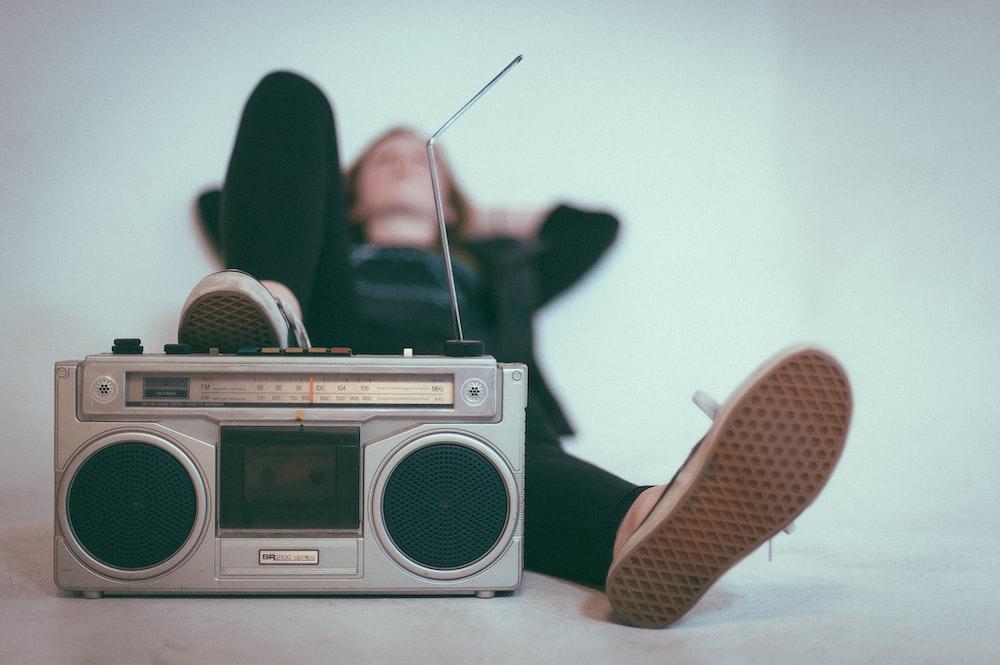 woman laying on bed near gray radio