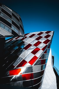 A partial exterior of a modern curvy architectural building, with red and clear glass panes