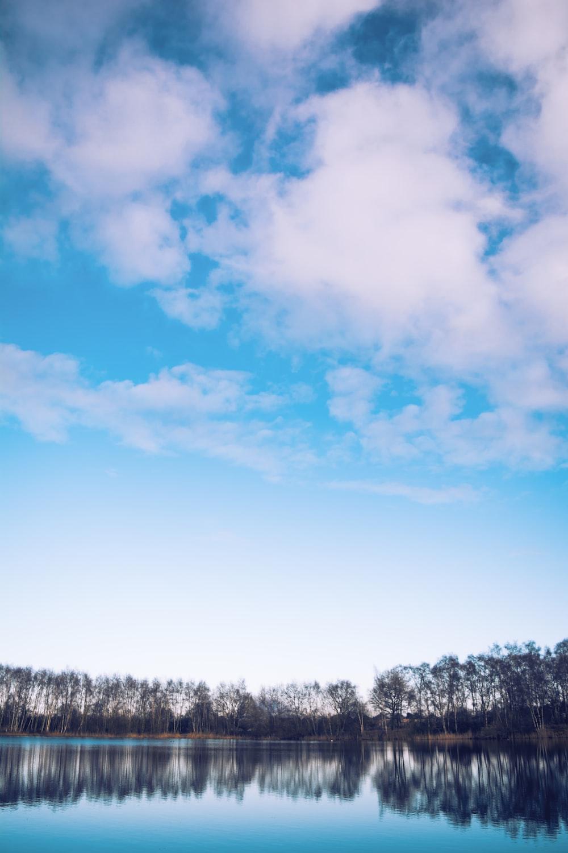calm body of water by treeline under blue skies
