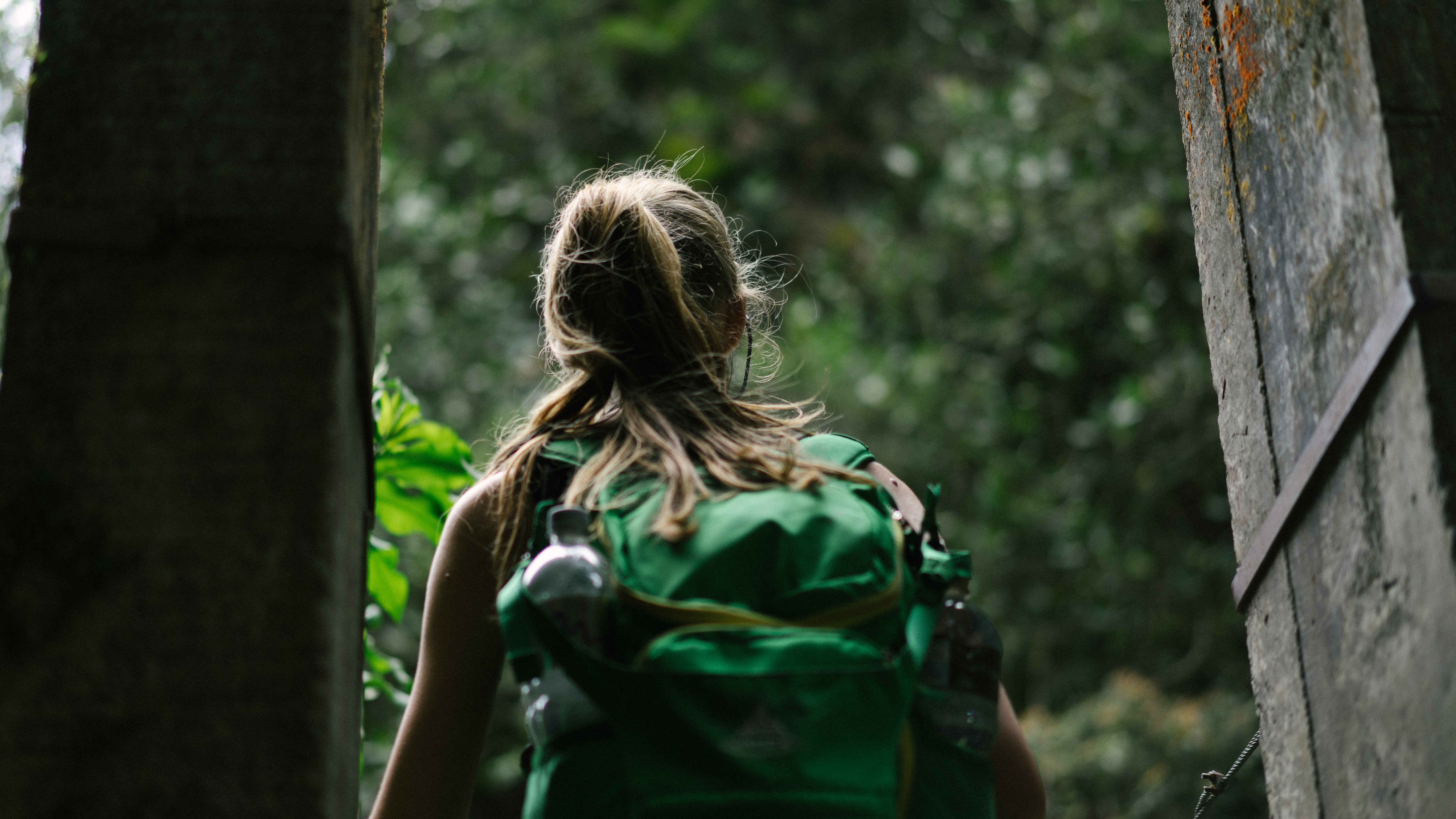 A woman with a ponytail, green backpack, and water bottle walks outside through wood doors